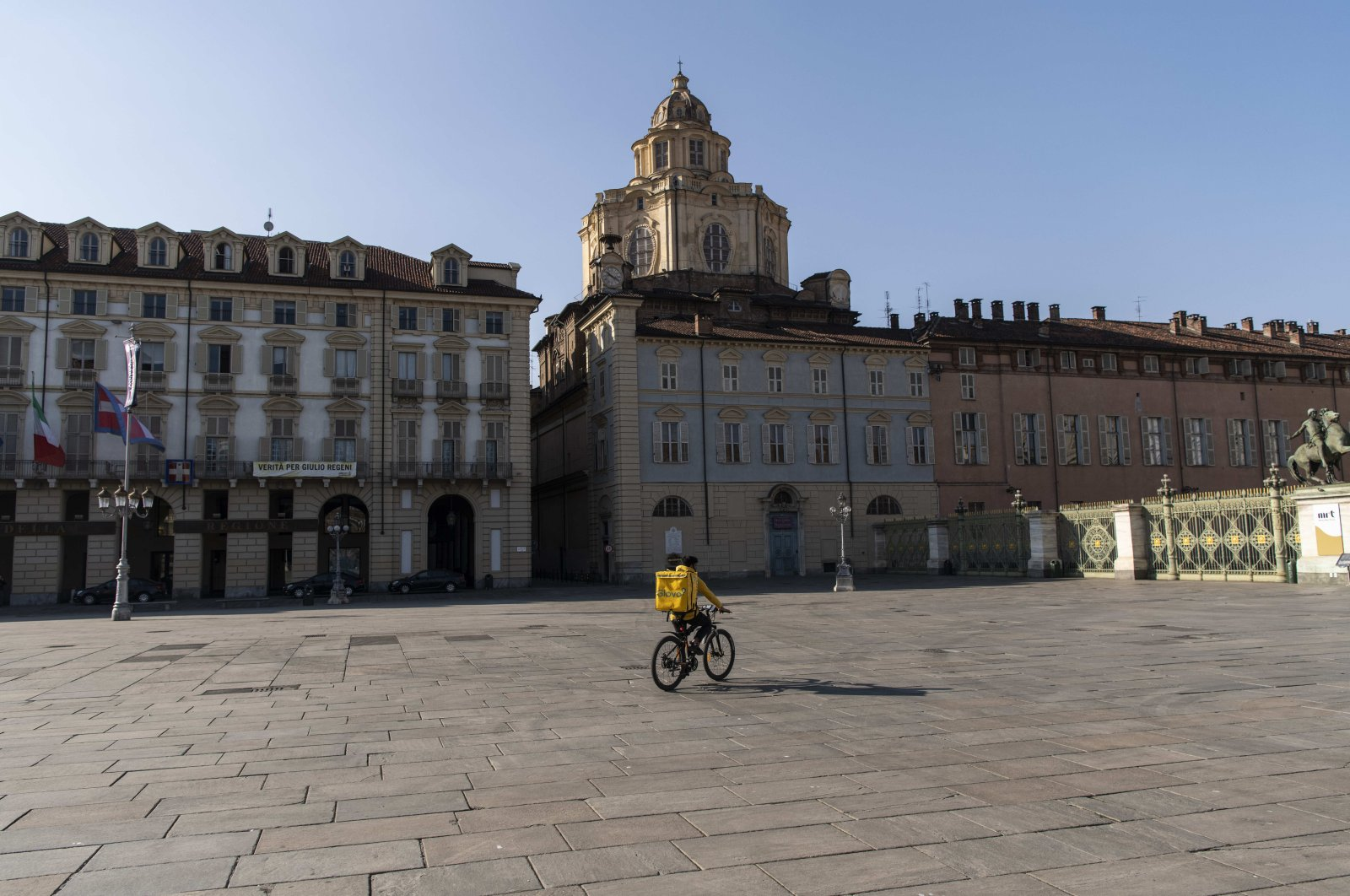 A food delivery rider pedals in deserted Piazza Castello, in Turin, Italy, Thursday, March 19, 2020.  (LaPresse via AP)