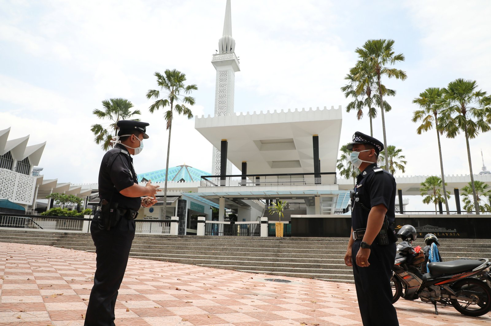 Police officers wearing protective masks stand guard outside National Mosque, after all, mosques in the country suspended Friday prayers during the movement control order due to the spread of the coronavirus disease (COVID-19), in Kuala Lumpur, Malaysia, March 20, 2020. (Reuters Photo)