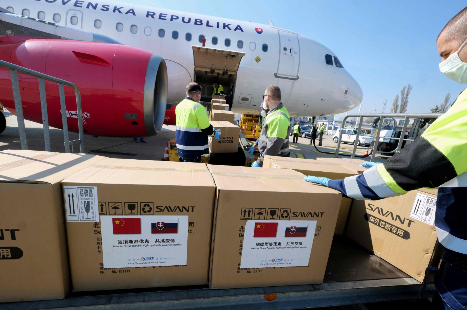 Slovak police officers unload a government Airbus-319, shortly after it arrived from Beijing, China, loaded with one hundred thousand of test kits for the novel coronavirus and one million face masks at M.R. Stefanilk airport, Bratislava, March 19, 2020. (AFP Photo)