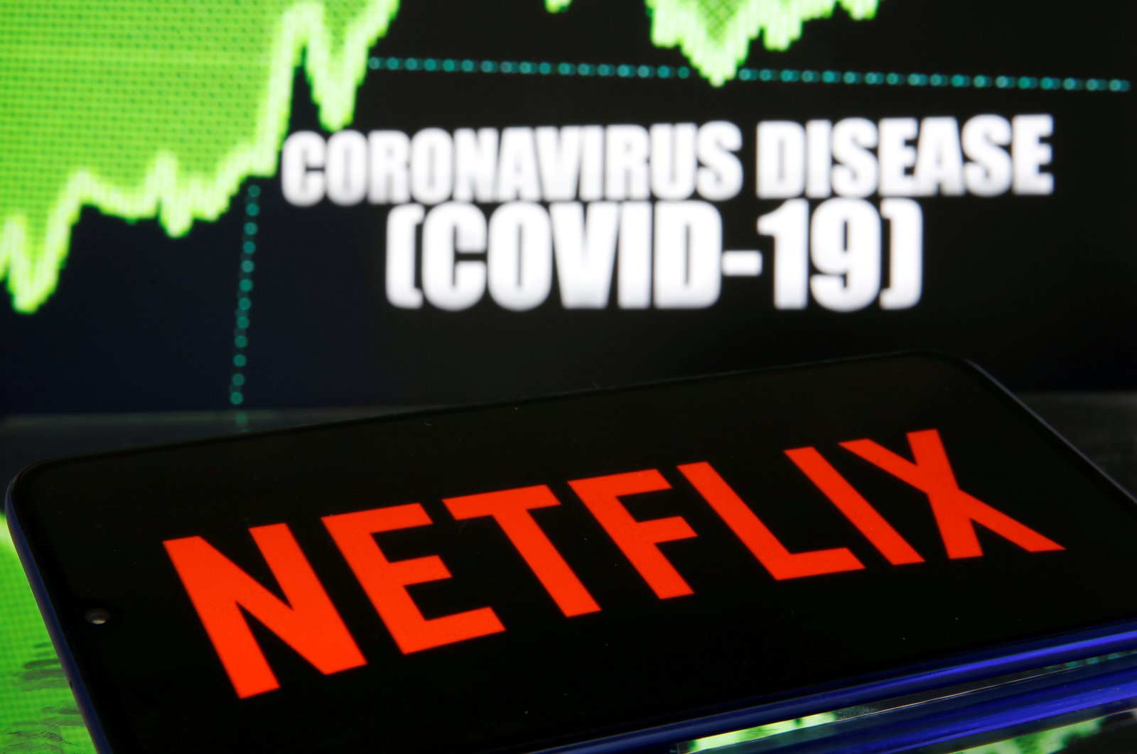 Netflix logo is seen in front of diplayed coronavirus disease (COVID-19) in this illustration taken March 19, 2020. (Reuters Photo)