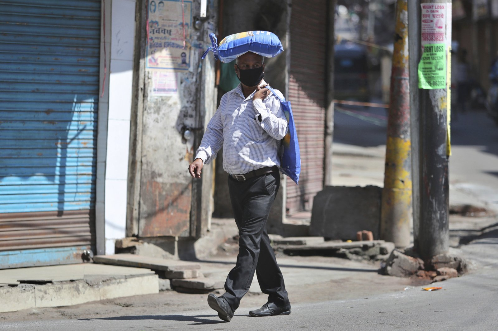 An Indian man, wearing a protective mask as a precaution against coronavirus, carries a bag of rice on his head during restrictions, Jammu, Friday, March 20, 2020. (AP Photo)