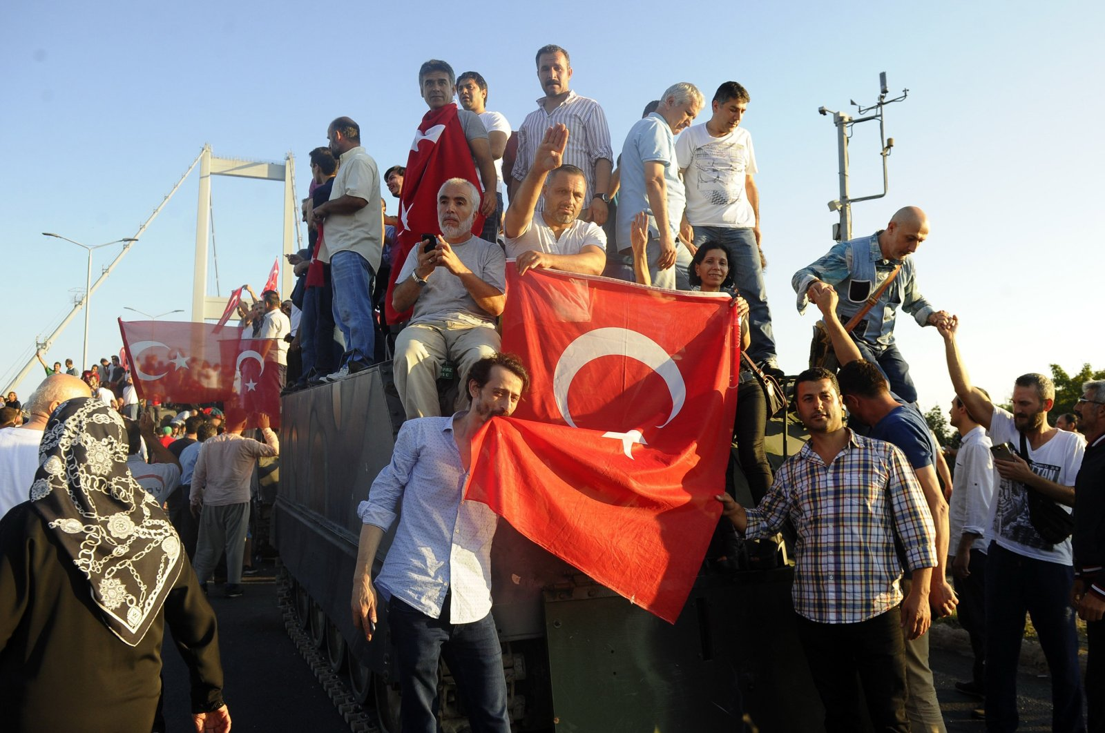 People pose with Turkish flag above an armored vehicle captured from putschists, Saturday, July 16, 2016, in Istanbul. (İHA Photo)