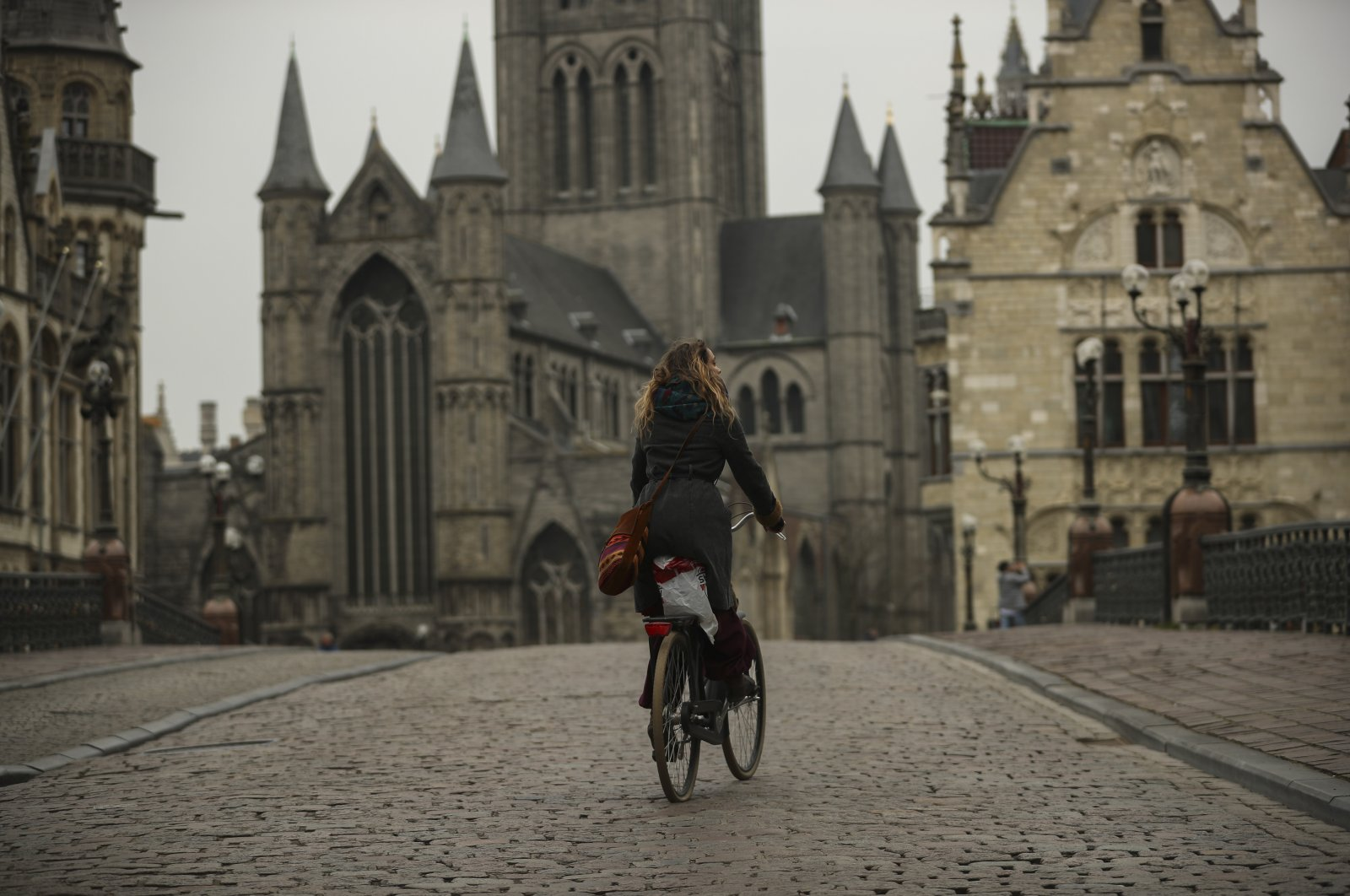 A woman rides a bicycle in downtown Ghent, Belgium, Thursday, March 19, 2020. (AP Photo)