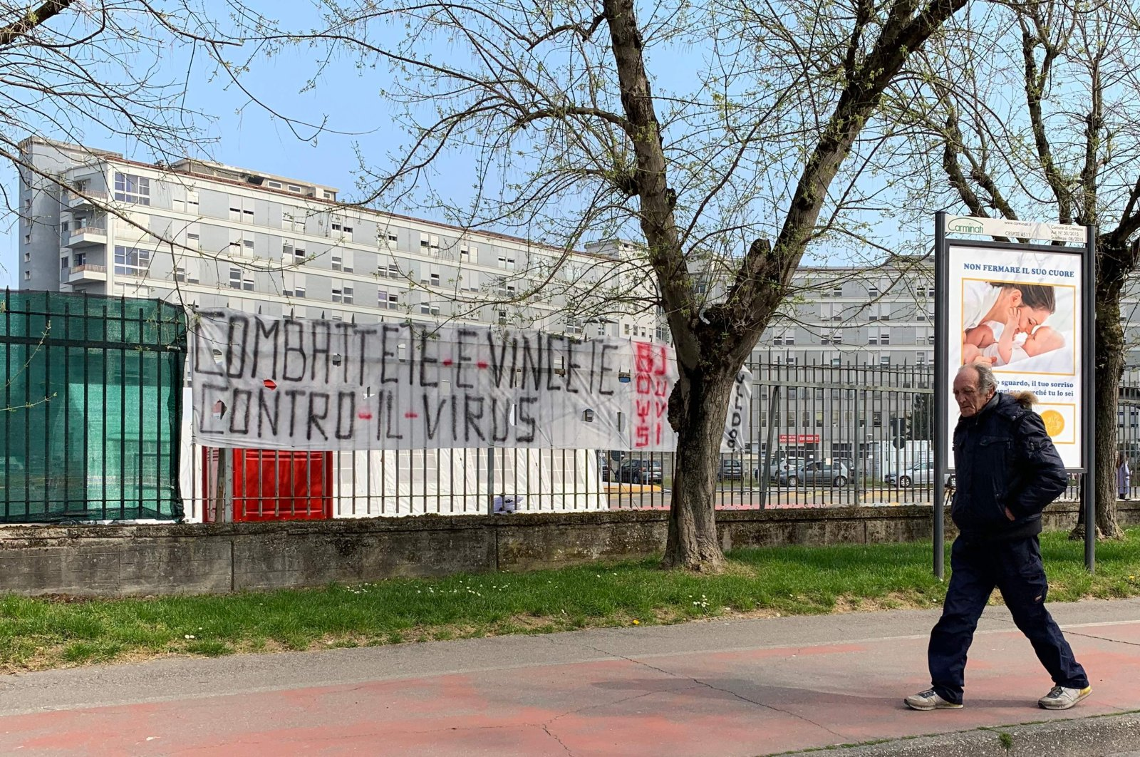 """A man walks past a banner reading """"fight and win against the virus,"""" outside the hospital of Cremona, Milan, Friday, March 20, 2020. (AFP Photo)"""
