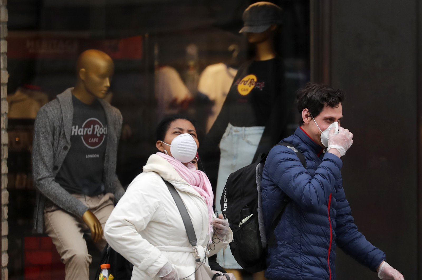People wearing face masks walk past closed shops in London, Friday, March 20. For most people, the new coronavirus causes only mild or moderate symptoms, such as fever and cough. (AP Photo)