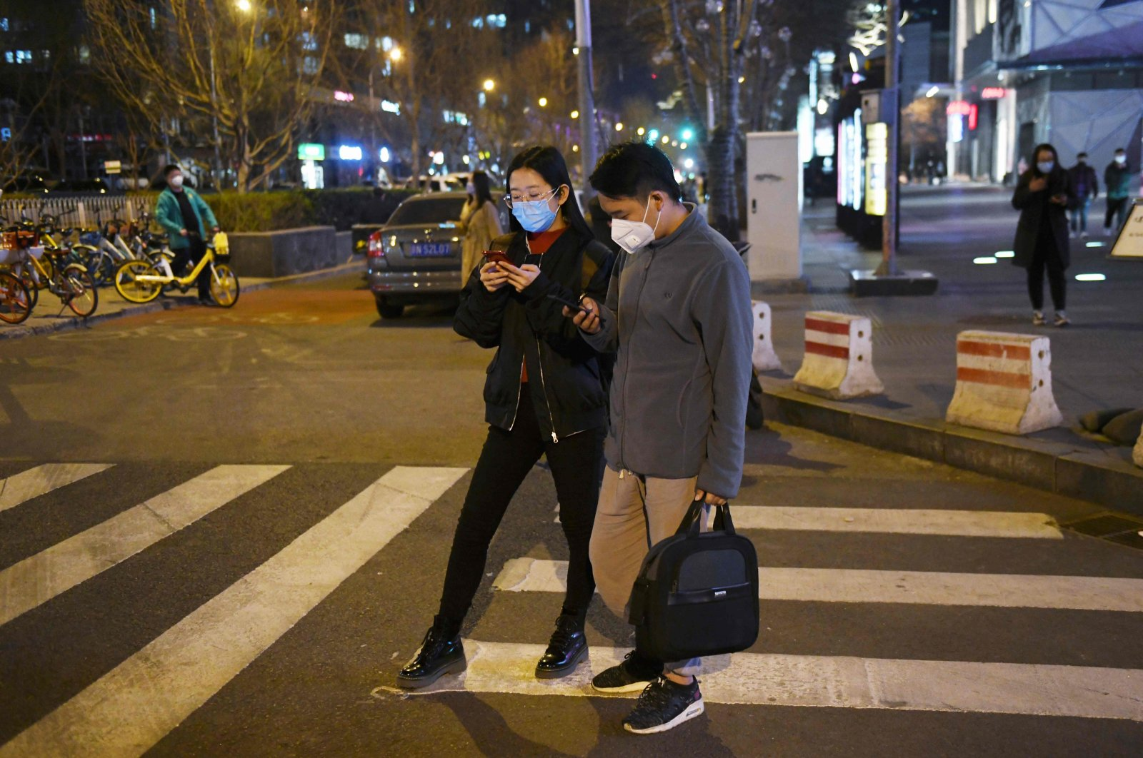 A couple, wearing masks amid concerns over the spread of the coronavirus, cross a road, Beijing. March 20, 2020. (AFP Photo)