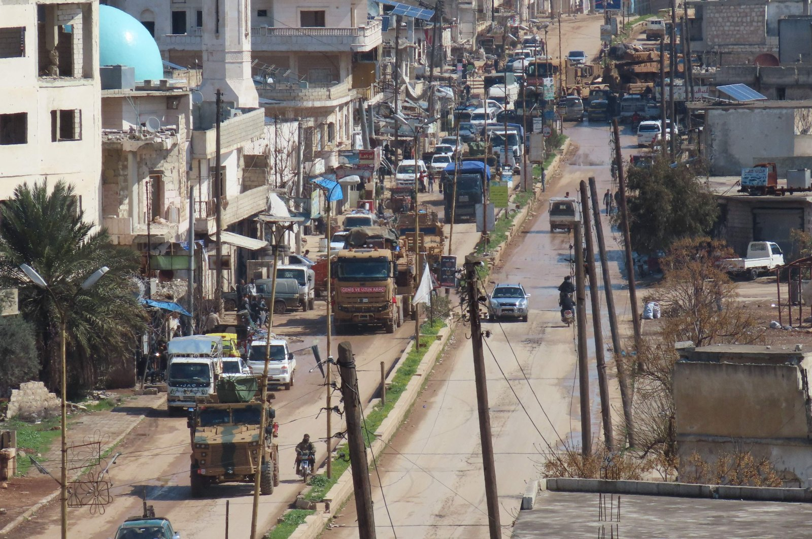 A Turkish military convoy drives through the town of Binnish, in Syria's northwestern Idlib province near the Turkish border, Thursday, March 19, 2020. (AFP)
