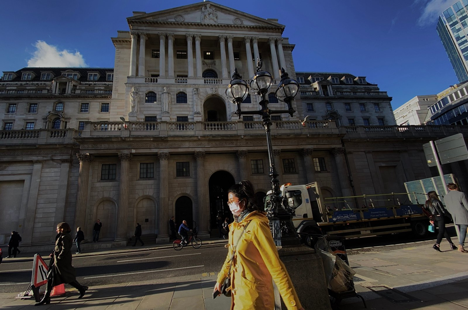 A pedestrian, wearing a protective face mask, walks past the Bank of England, London, Wednesday, March 11, 2020. (AFP Photo)