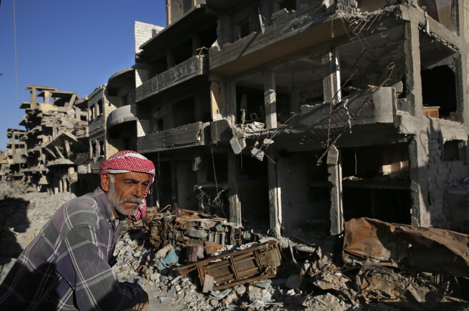 A Syrian man stands between buildings destroyed last summer during fighting between the U.S.-backed YPG and Daesh, in Raqqa, April 5, 2018. (AP)