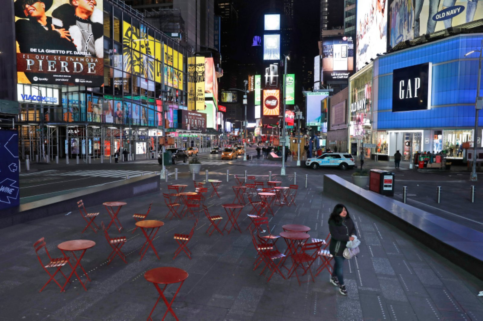 A woman walks through a lightly trafficked Times Square in New York, Monday, March 16, 2020. (AP Photo)