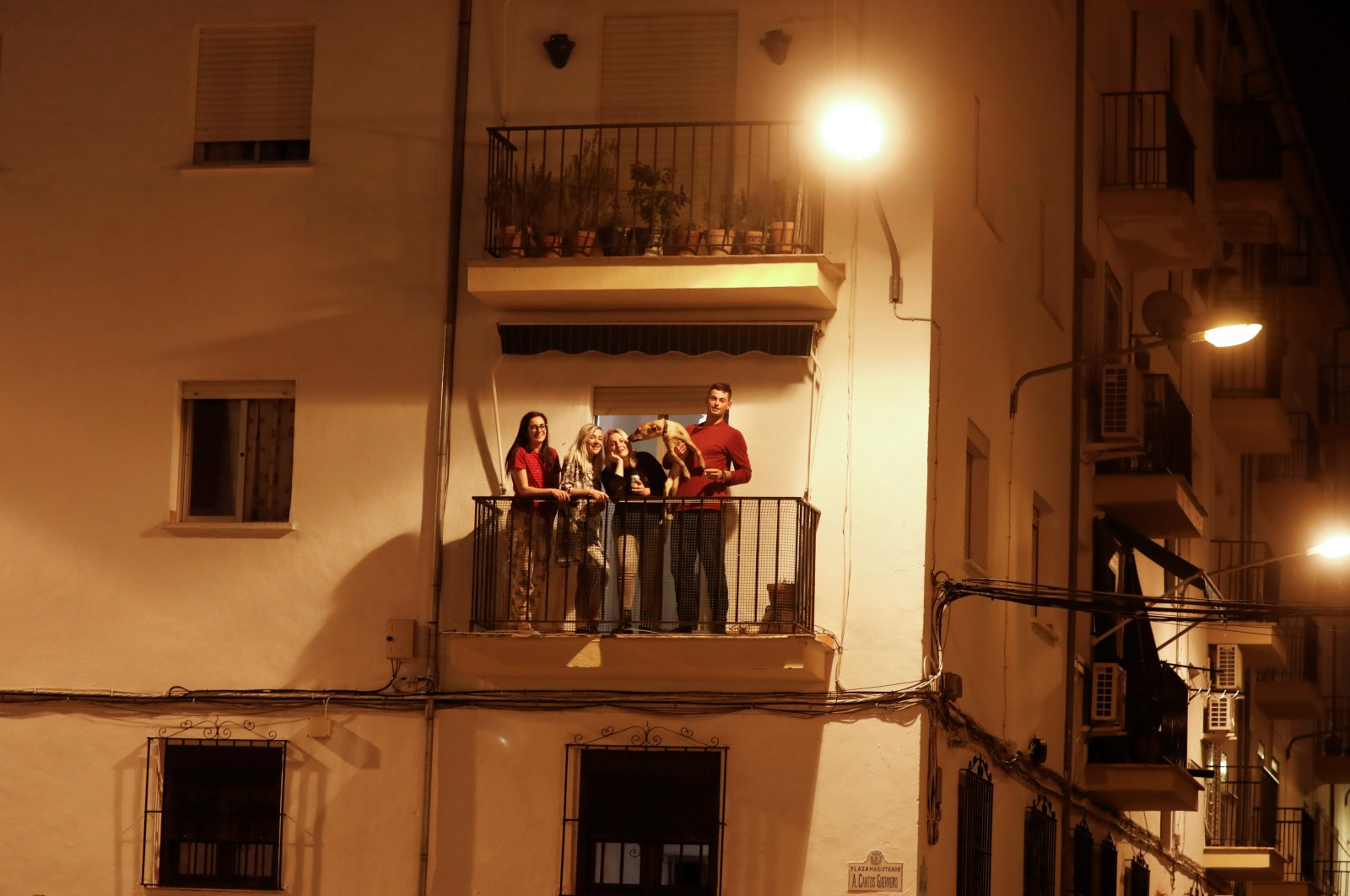 Youngers pose for a photo on a balcony of their shared flat as they remain confined inside it due to the coronavirus outbreak, in downtown Ronda, southern Spain March 14, 2020. (Reuters Photo)