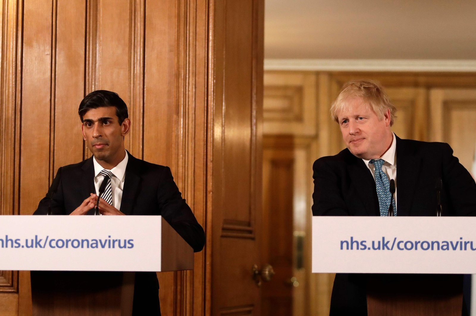 Britain's Chancellor of the Exchequer Rishi Sunak (L) and Britain's Prime Minister Boris Johnson (R) attend a news conference addressing the government's response to the novel coronavirus COVID-19 outbreak, inside 10 Downing Street in London on March 17, 2020. (AFP Photo)