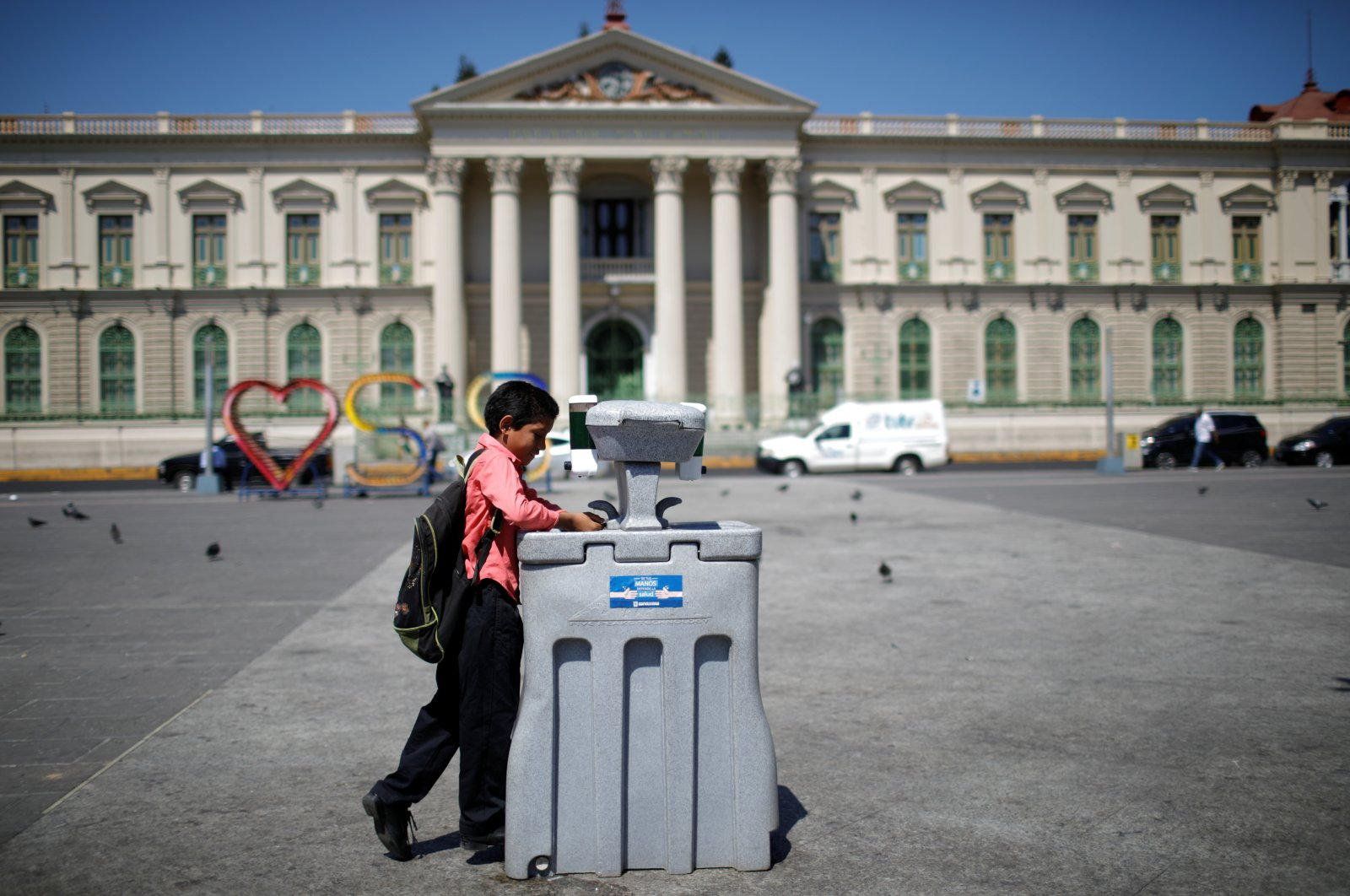 A boy washes his hands in a portable hand-washing station as part of the steadily stricter measures to prevent a possible spread of the coronavirus disease (COVID-19), at the Metropolitan Cathedral, in San Salvador, El Salvador, March 15, 2020. (Reuters Photo)
