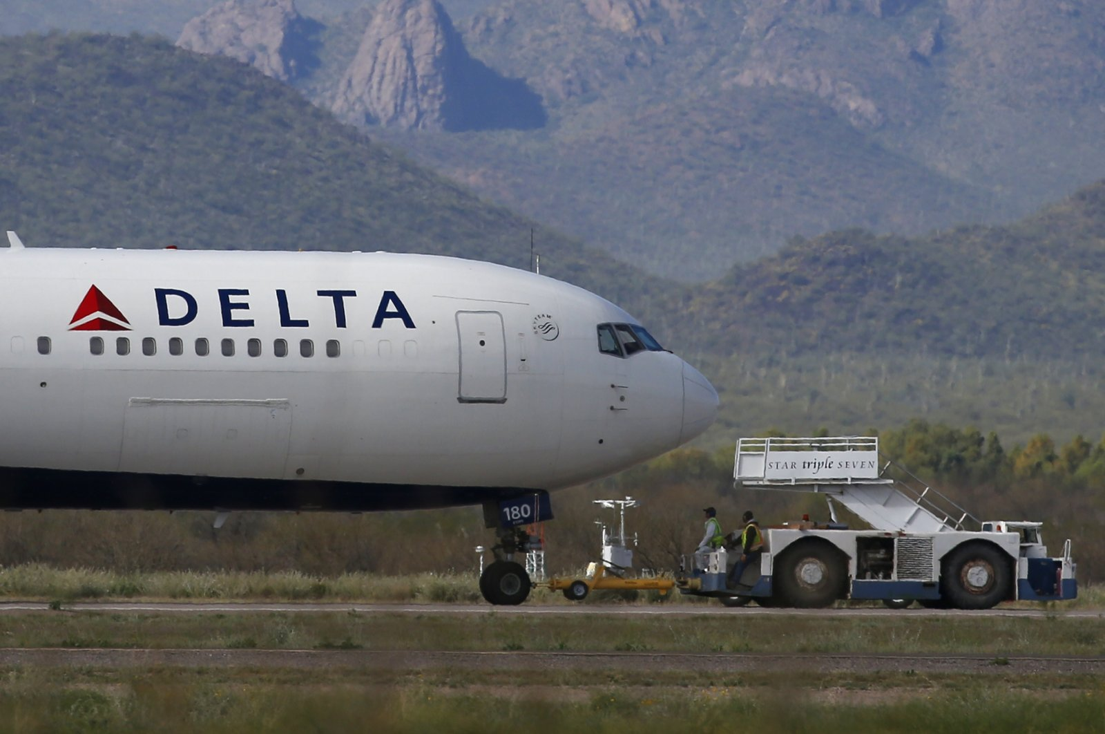 A recently landed Delta Air Lines airplane is worked on by ground crew at Pinal Airpark Wednesday, March 18, 2020. (AP Photo)