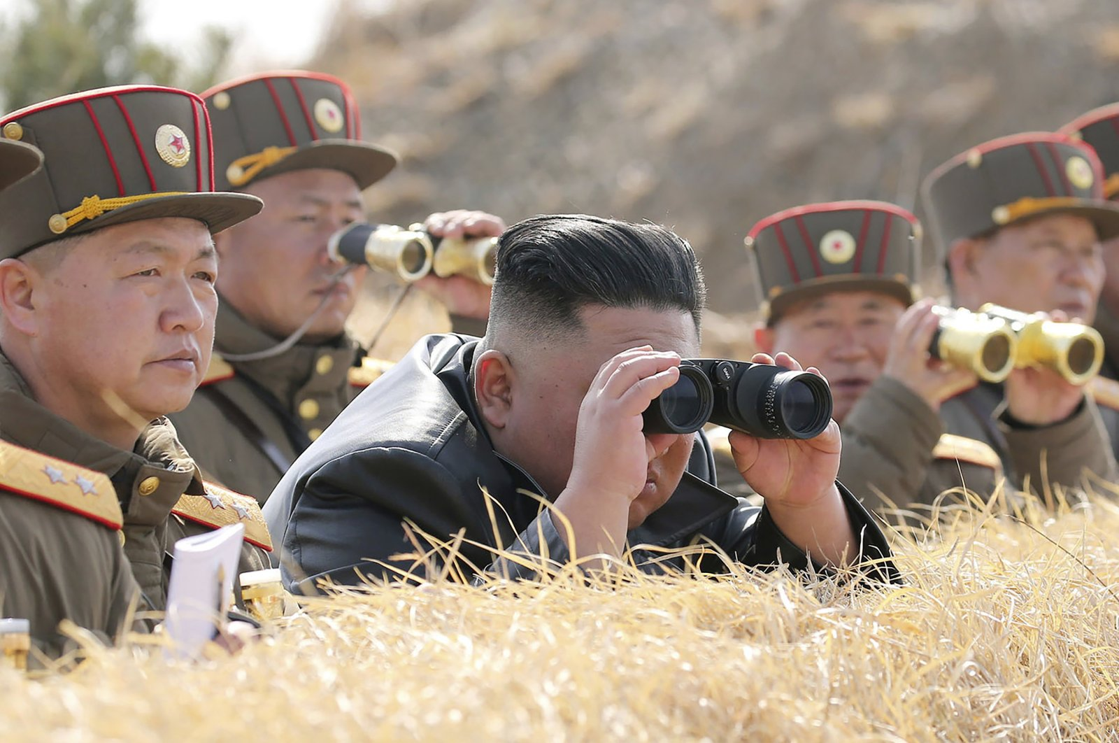 In this Friday, March 20, 2020, photo provided by the North Korean government, North Korean leader Kim Jong Un supervises an artillery firing competition between army units in the country's west in North Korea. (Korean Central News Agency via AP)