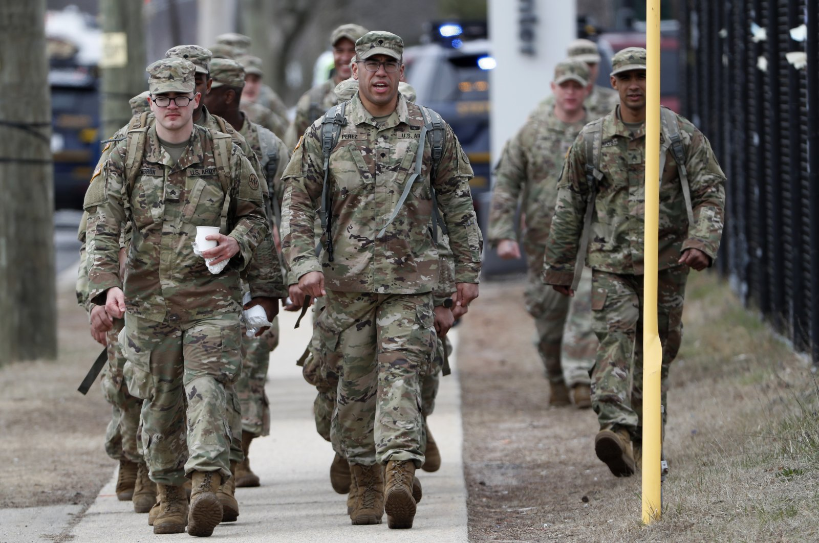 National Guard personnel march in formation as they leave duty after working Thursday, March 19, 2020, at a state-managed coronavirus drive-through testing site that just opened on Staten Island in New York. (AP Photo)