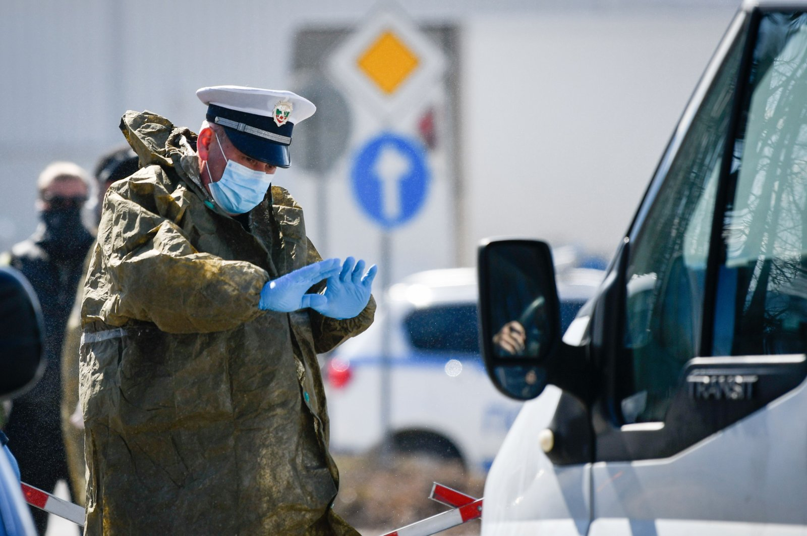 A police officer wearing a protective suit gestures at a checkpoint at the entrance of the Bansko ski resort in Bulgaria, March 18, 2020. (AFP Photo)