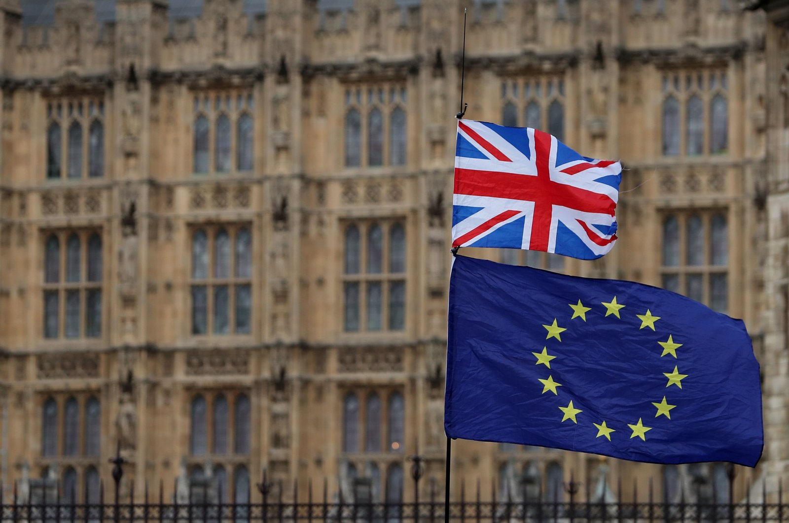 In this file photo taken on Jan. 23, 2019 an anti-Brexit activist waves a Union and a European Union flag as they demonstrate outside the Houses of Parliament in central London. (AFP Photo)