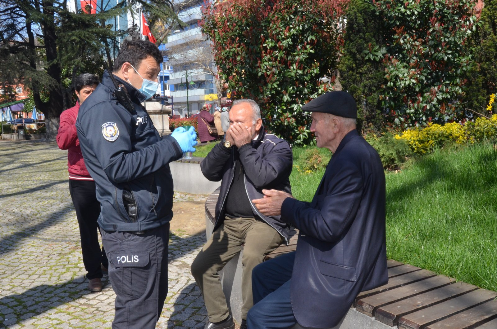 Police officer in Turkey's Zongulak offers elderly Turkish cologne and tells them that they are supposed to be at home, offers ride home, March 21, 2020. (IHA Photo)