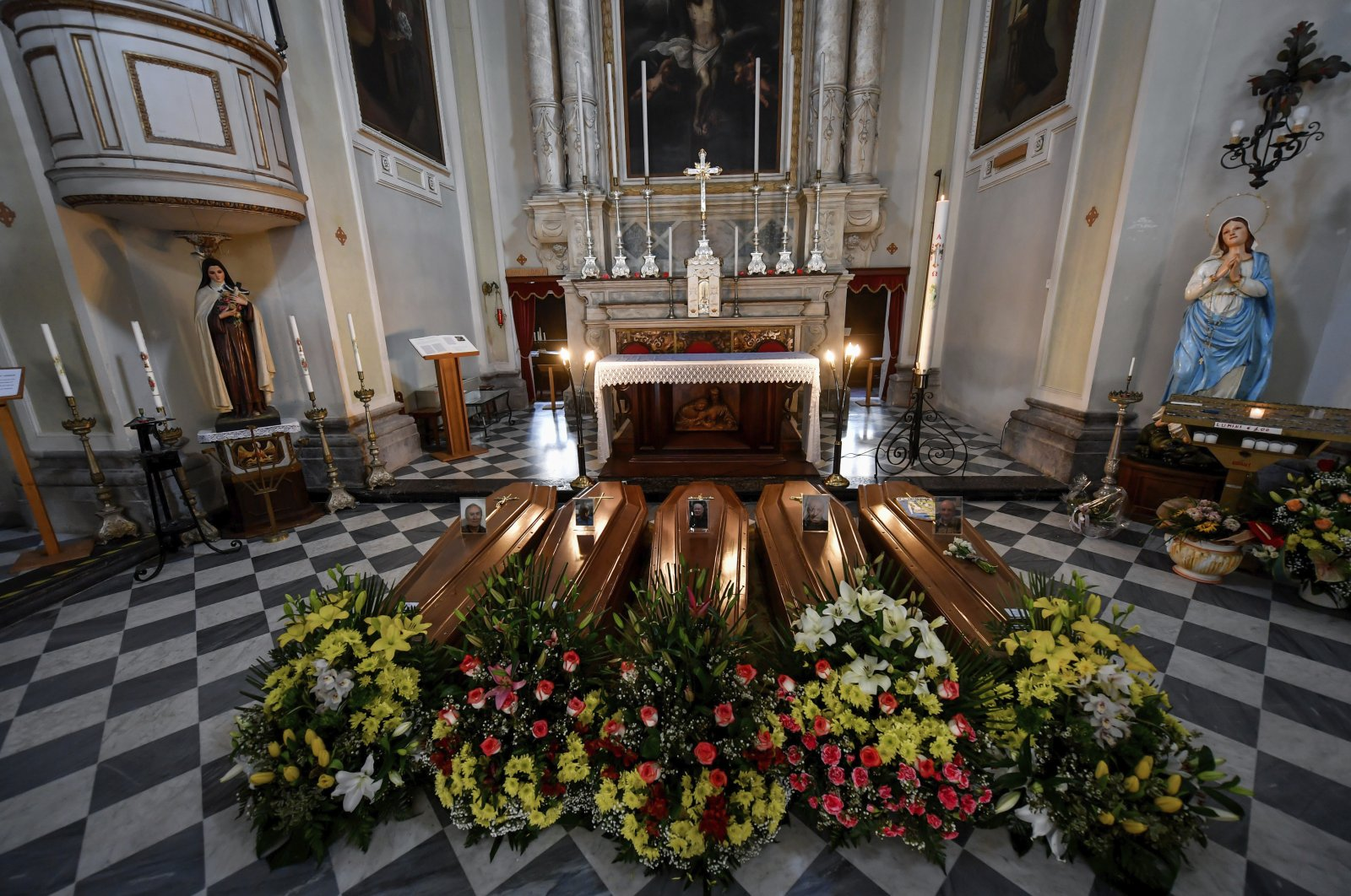 Coffins wait to be transported to cemetery, in the church of Serina, near Bergamo, Northern Italy, Saturday, March 21, 2020. (AP Photo)