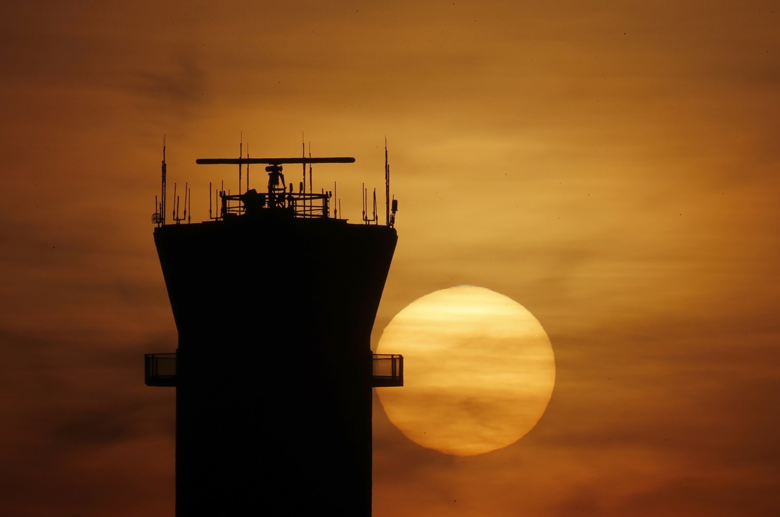 The sun sets behind the FAA Control Tower at Chicago's Midway International Airport on Tuesday, March 17, 2020, in Chicago. (AP Photo)