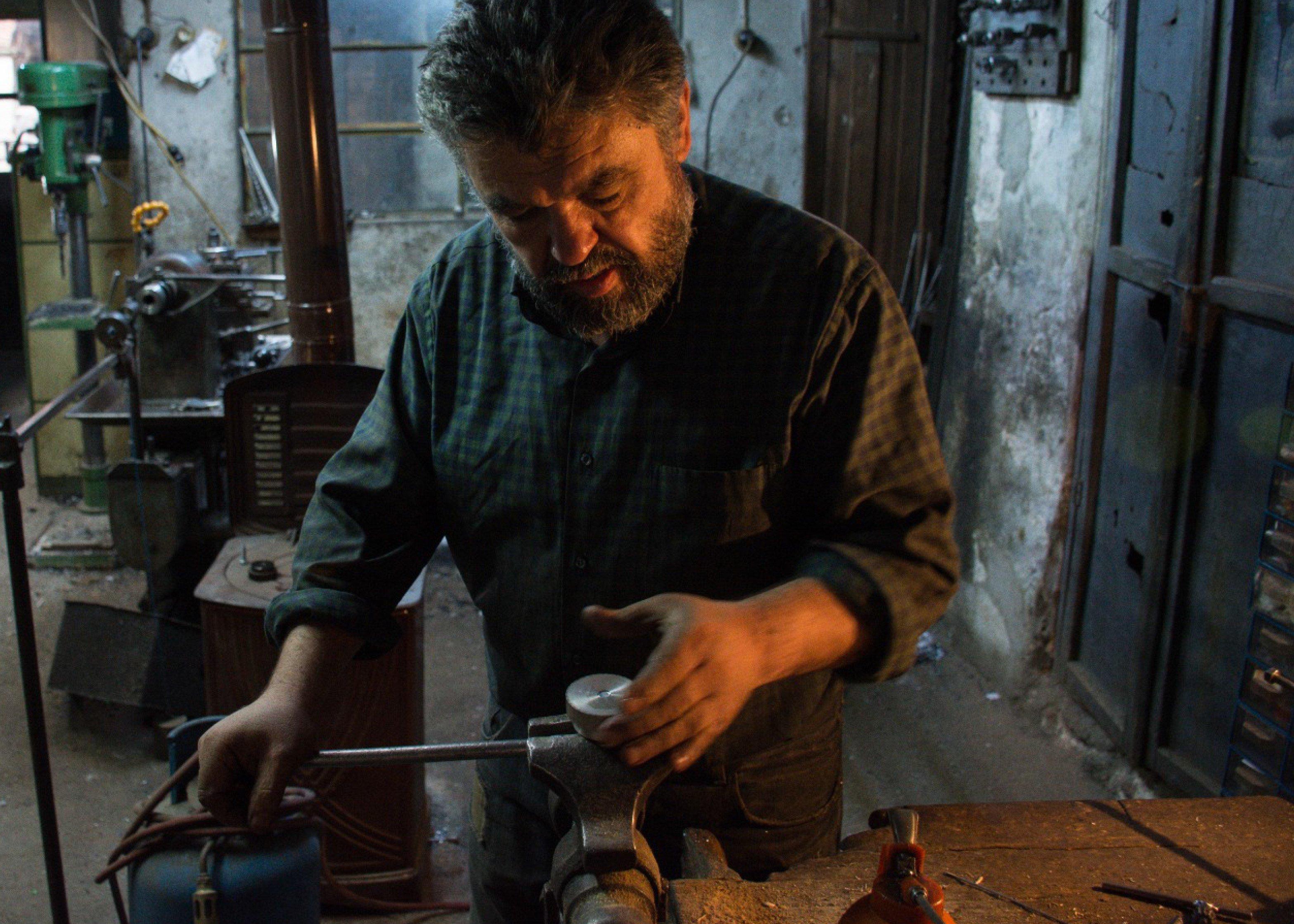 Aydoğan Aslan uses a lathe machine in his workshop. (AA Photo)