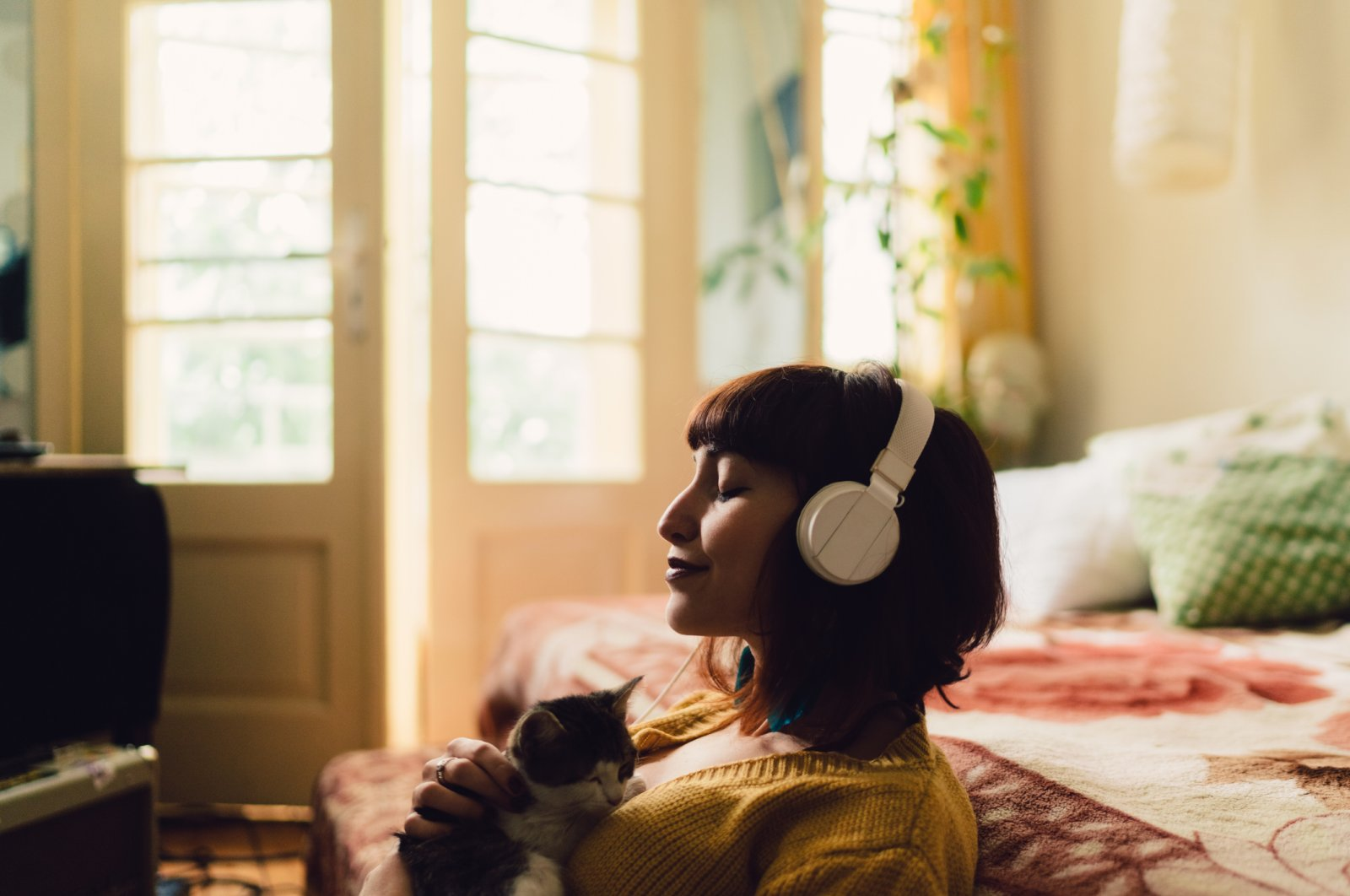 Teenage girl listens to audio while relaxing at home with her cat.