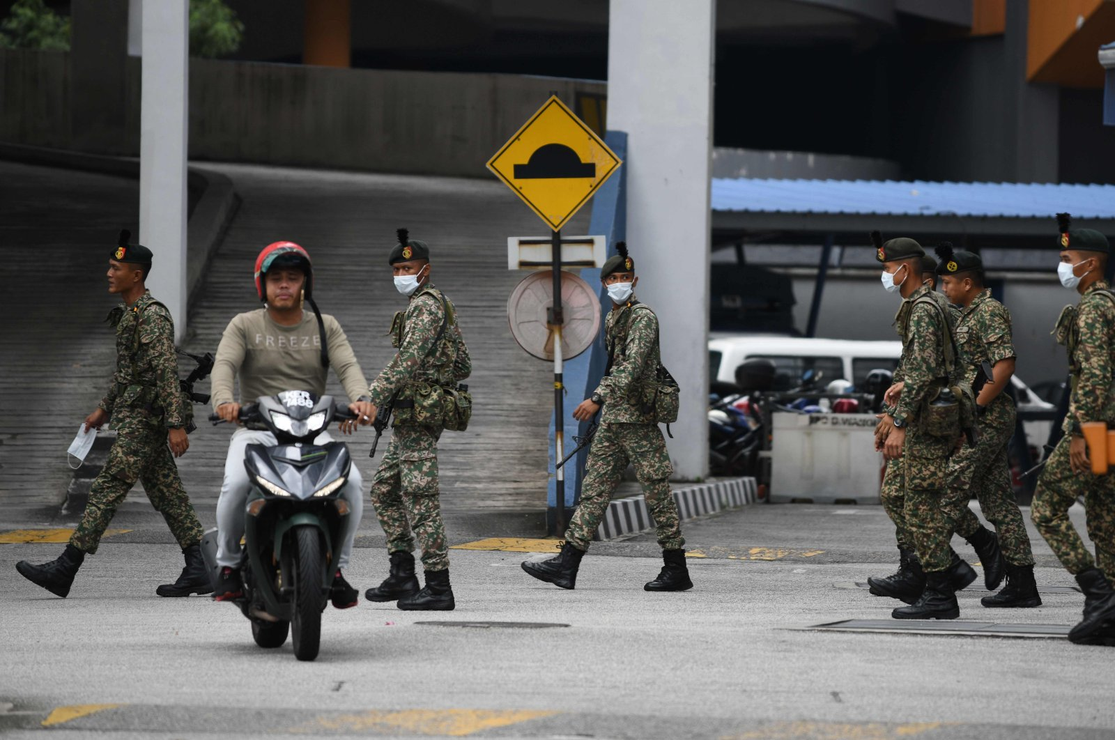 A motorcyclist rides past soldiers wearing face masks inside a police station during the control of movement in Kuala Lumpur amid fears over the spread of the coronavirus, Sunday, March 22, 2020. (AFP Photo)