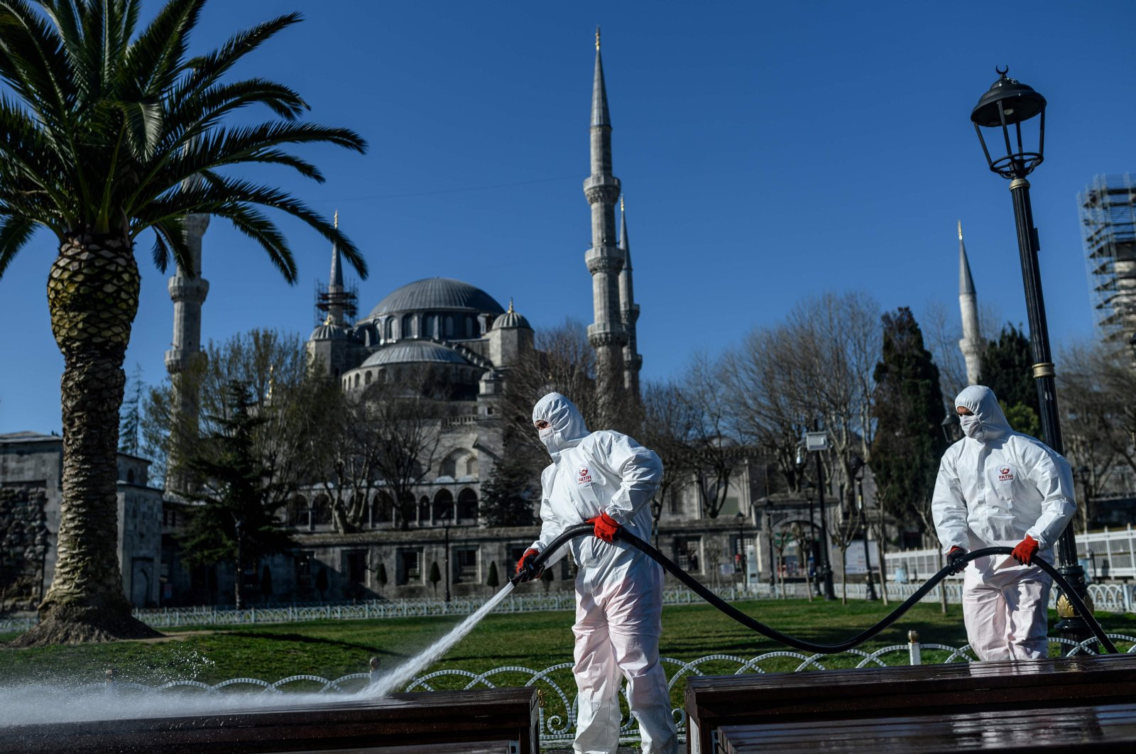 Members of the Fatih Municipality disinfect Istanbul's Sultanahmet square with the Blue Mosque seen in the background to prevent the spread of the new coronavirus on March 21, 2020. (AFP Photo)