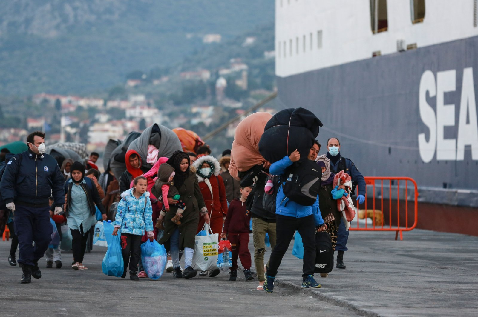 Migrants arrive at the port of Mytilene on the Greek island of Lesbos to be transferred to a closed camp in northern Greece, March 20, 2020. (AFP Photo)