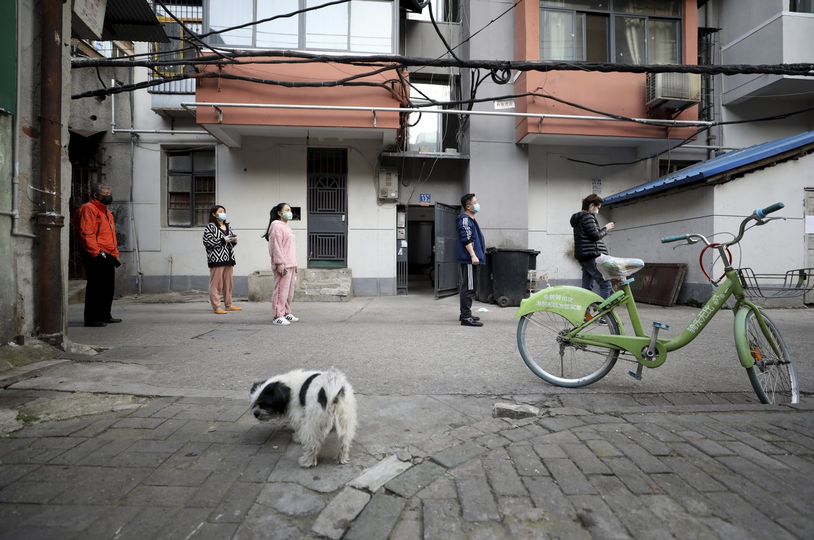 People stand in a spaced line as they wait to buy pork at the entrance gate of a closed residential community in Wuhan in central China's Hubei Province, Wednesday, March 18, 2020. (AP Photo)