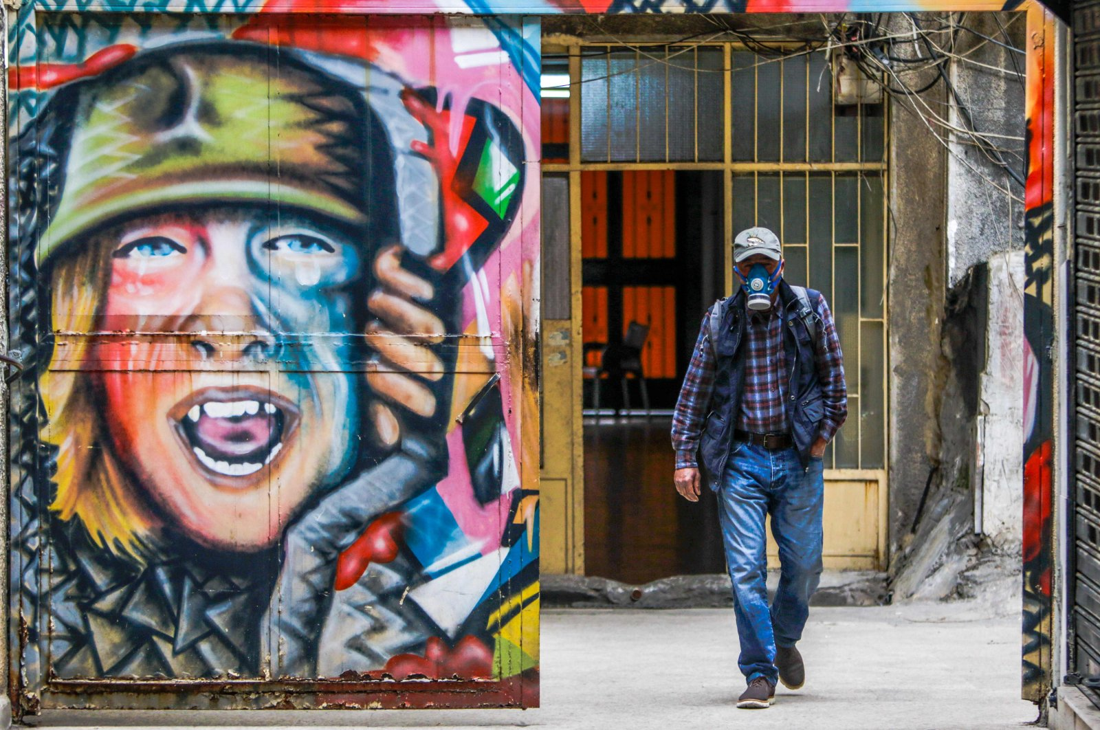 A man, wearing facial gas mask as part of health safety measures related to the spread of COVID-19, walks past a graffiti in the northern port city of Tripoli, Monday, March 16, 2020. (AFP Photo)