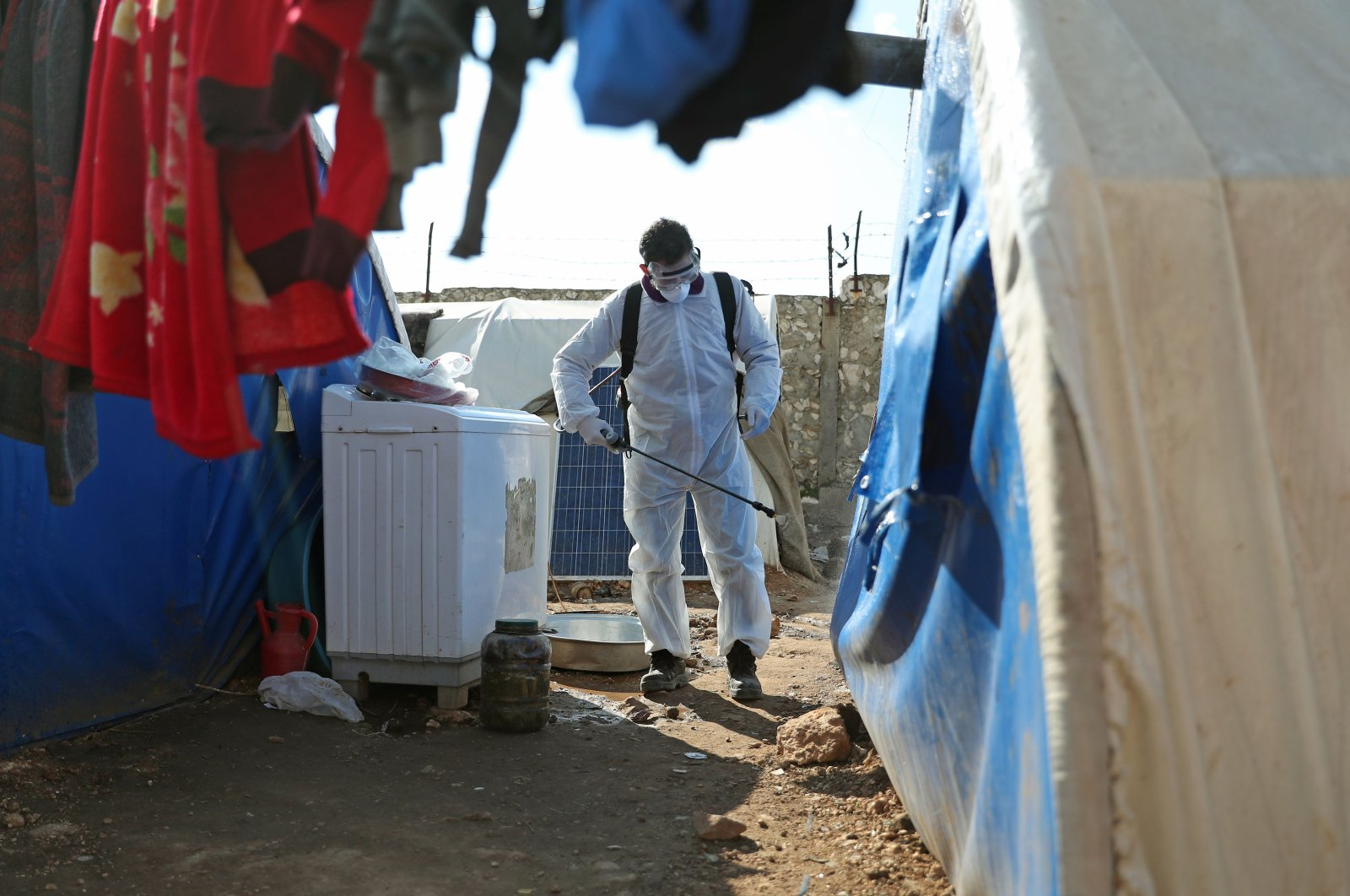 A member of the Syrian Violet NGO disinfects tents at a camp for displaced people in Kafr Jalis village, north of Idlib city, on March 21, 2020, as a preventive measure against the spread of the coronavirus. (AFP Photo)