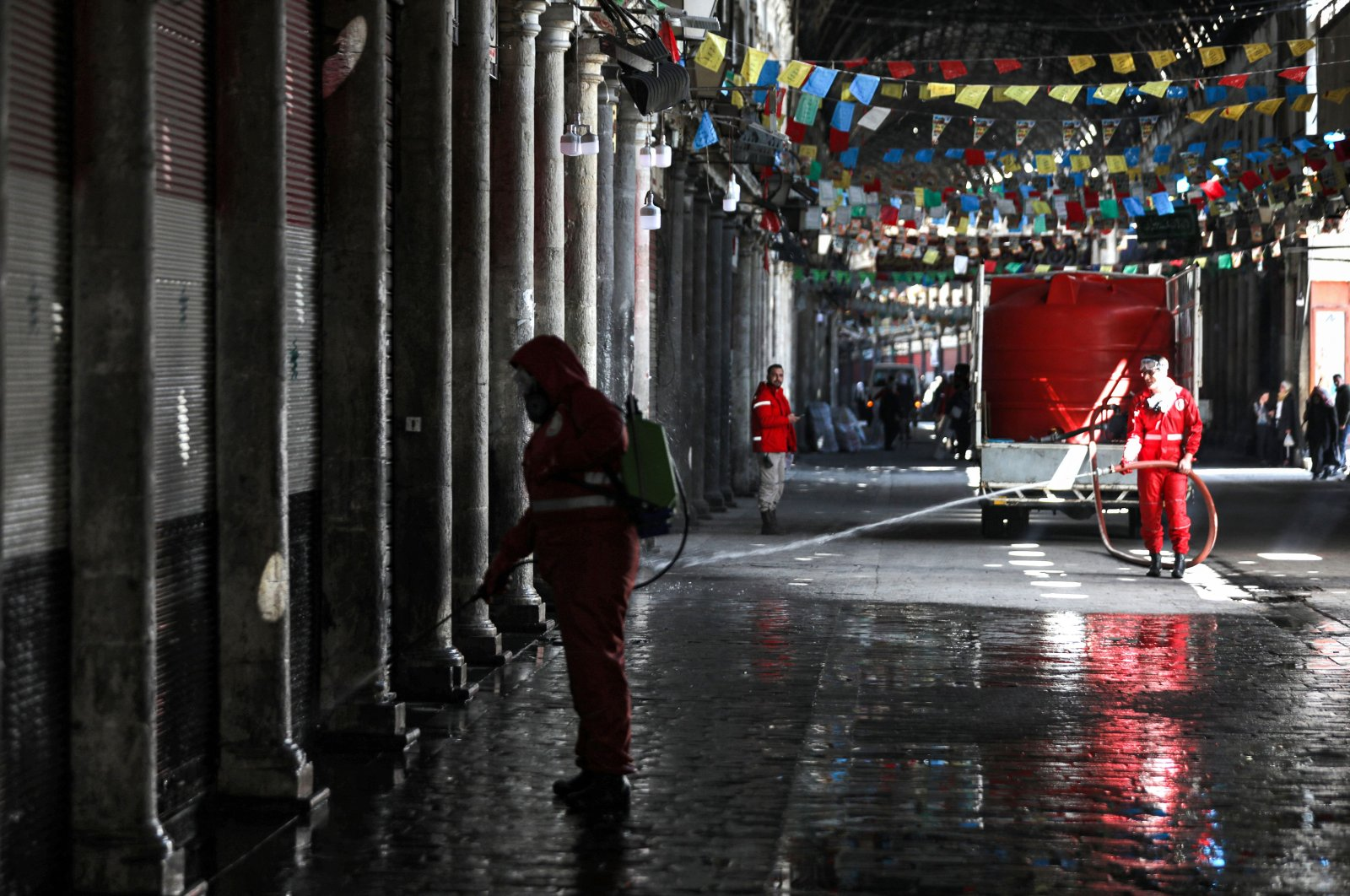 A Syrian Red Crescent member sprays disinfectant along an alley of the historic Hamidiyah souk (market) in the old city of Syria's capital Damascus on March 22, 2020, as part of efforts against the coronavirus pandemic. (AFP Photo)