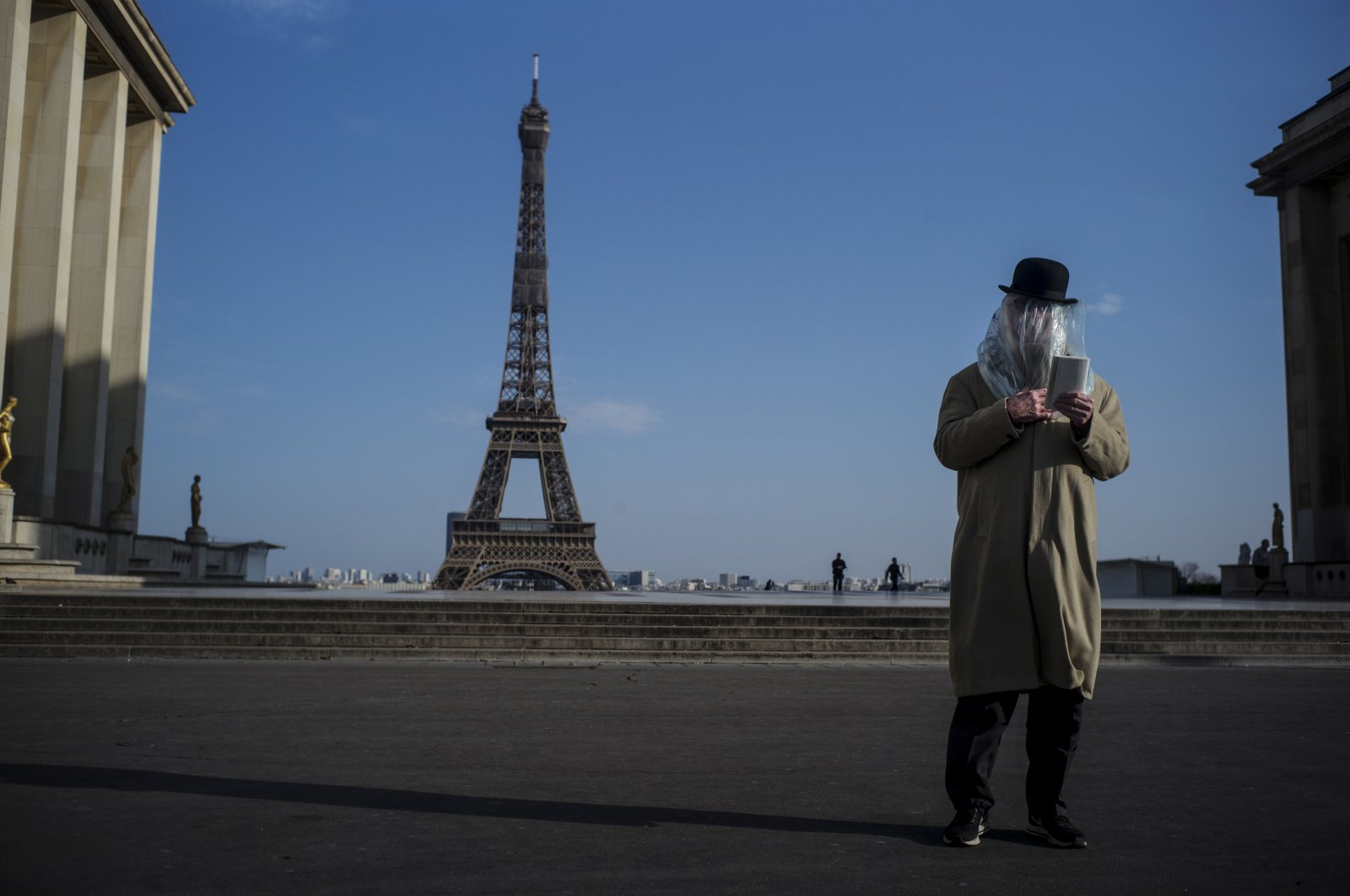 A man has his head covered with a plastic bag for protection reads a book in front of the Eiffel tower in Paris, France, 22 March 2020. (EPA Photo)