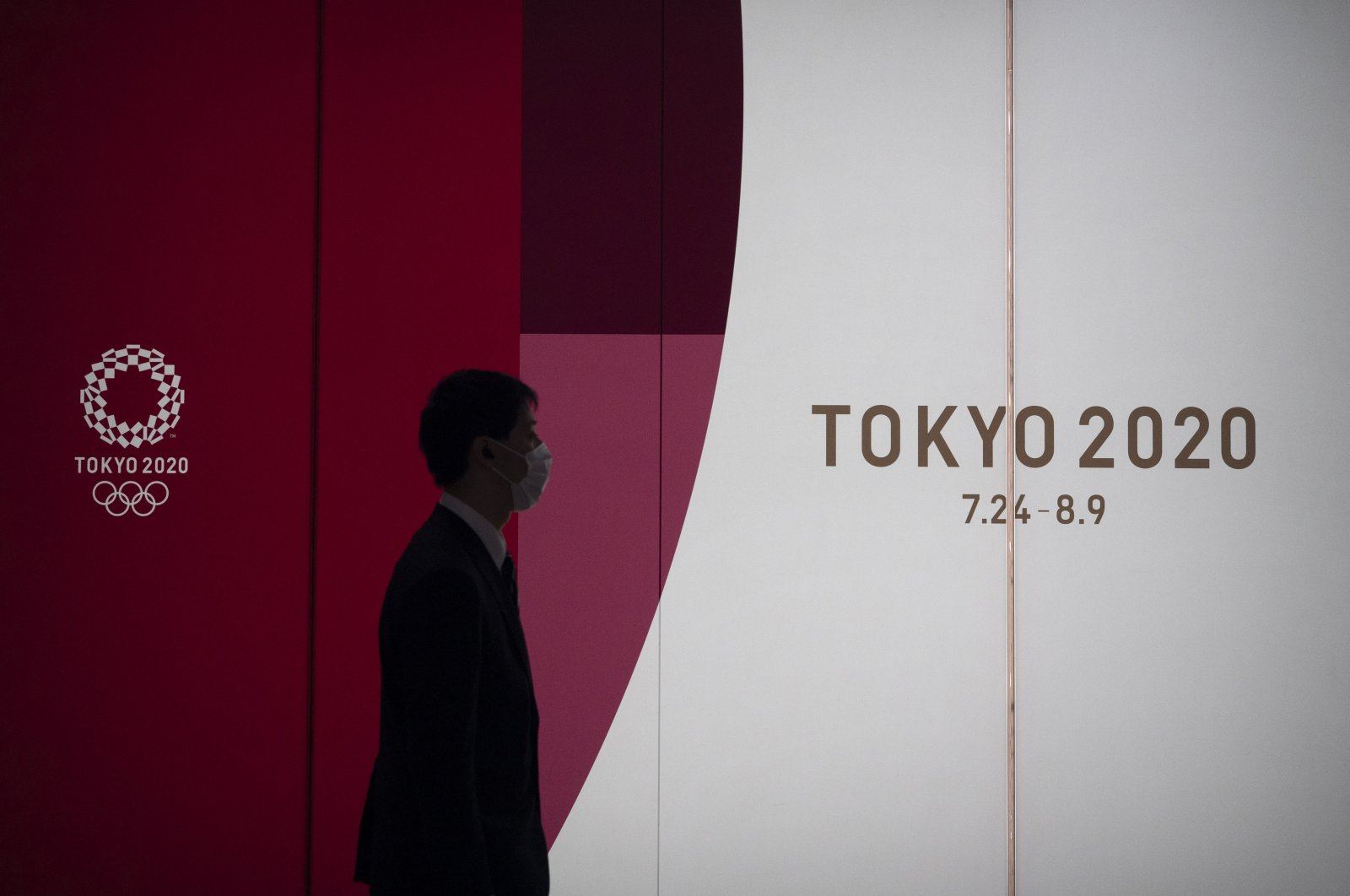 A man walks past a large display promoting the Tokyo 2020 Olympics, in Tokyo, Monday, March 23, 2020. (AP Photo)
