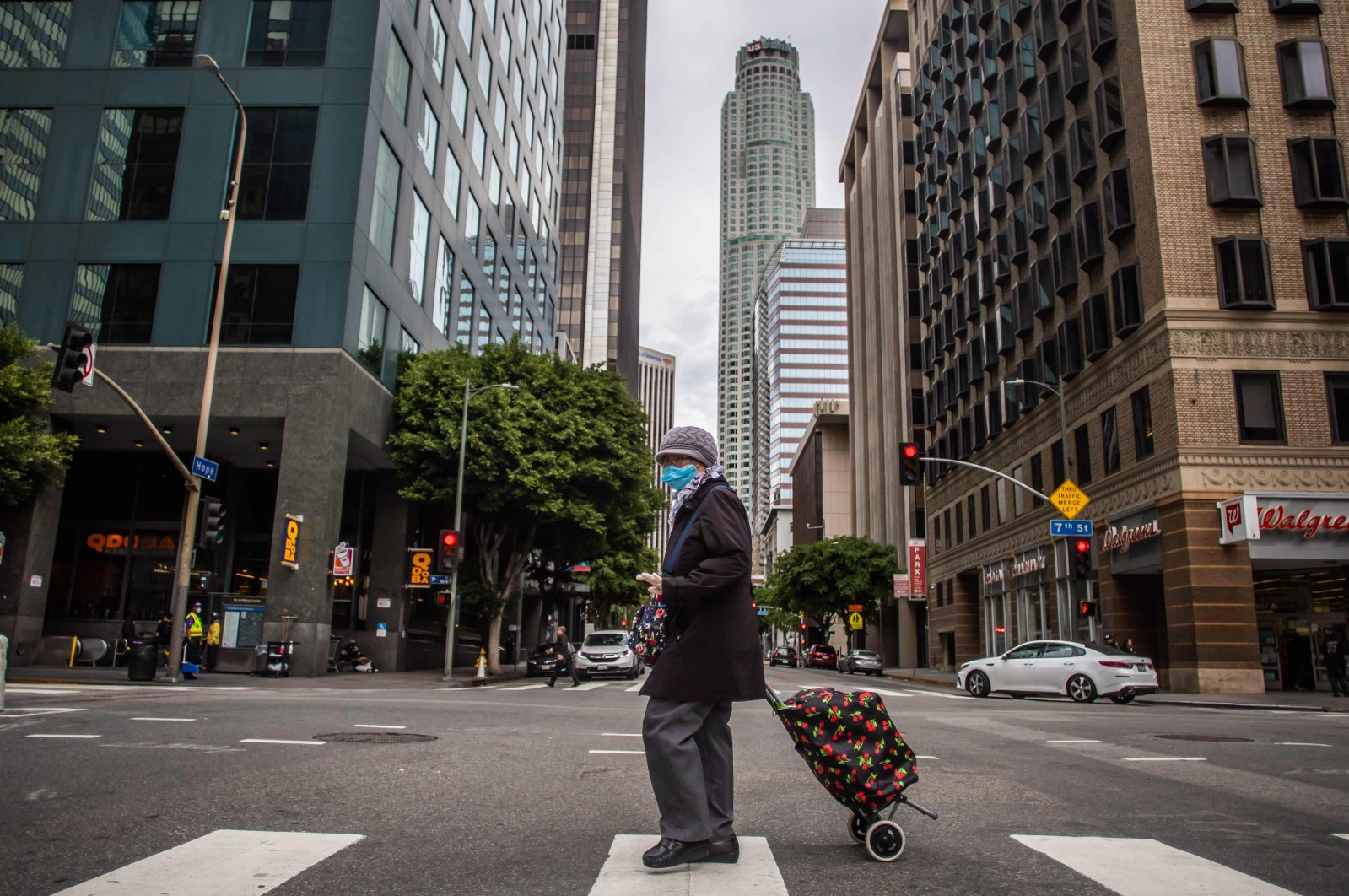 A woman wearing a mask walks in downtown Los Angeles, Sunday, March 22, 2020. (AFP Photo)