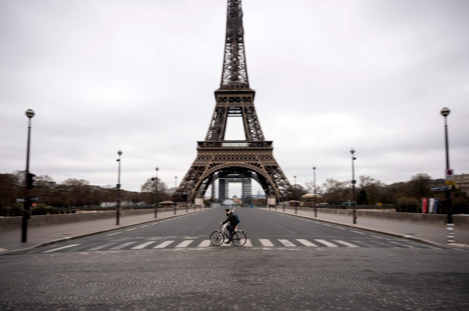 A man rides his bike on empty streets facing the Eiffel Tower, Paris, Saturday, March 21, 2020. (AFP Photo)