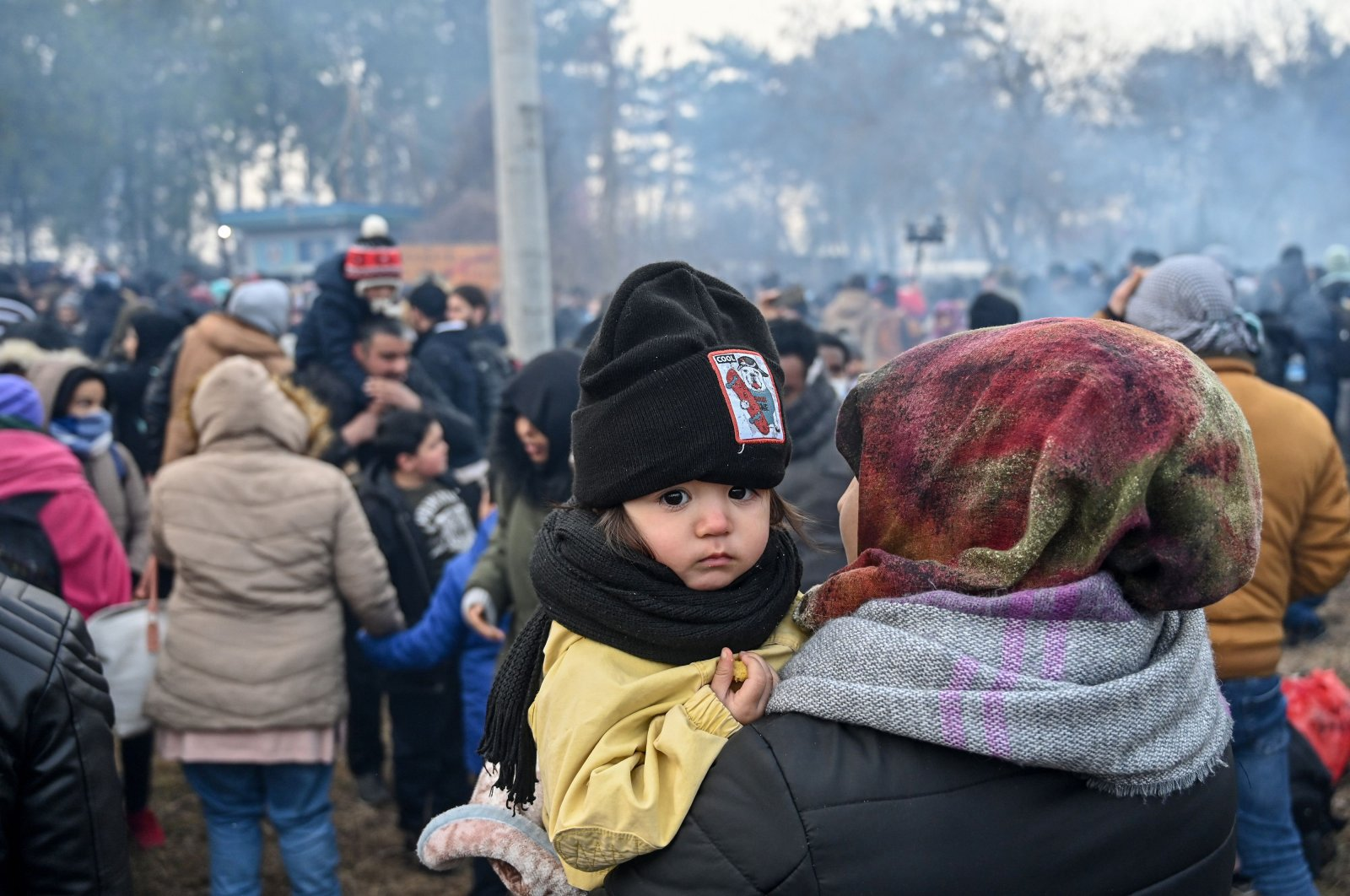 A child looks on as migrants wait to pass the buffer zone at the Turkey-Greece border, at Pazarkule, in Edirne district, Feb. 29, 2020. (AFP Photo)