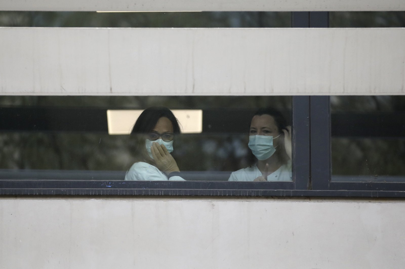 Medical staff watch people waiting in line to get a coronavirus test outside the La Timone hospital, Marseille, Monday, March 23, 2020. (AP Photo)