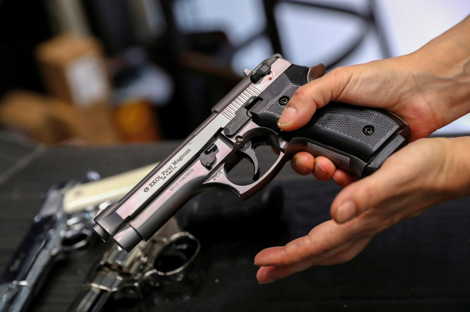 A Hungarian vendor shows an Ekol Firat Magnum gas pistol at a gun shop where people queued up to buy weapons for protection during the coronavirus pandemic, in Budapest, March 20, 2020. (Reuters Photo)