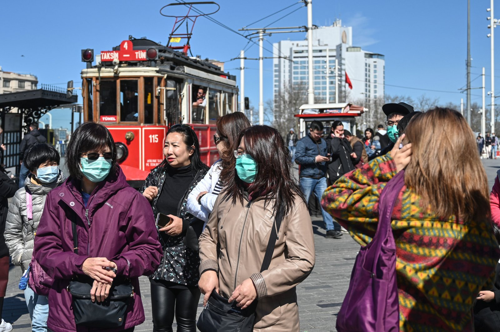 Tourists wear protective face masks as they walk at Taksim Square as the nation tries to limit the spread of the new coronavirus, in Istanbul, Tuesday, March 17, 2020. (AFP Photo)