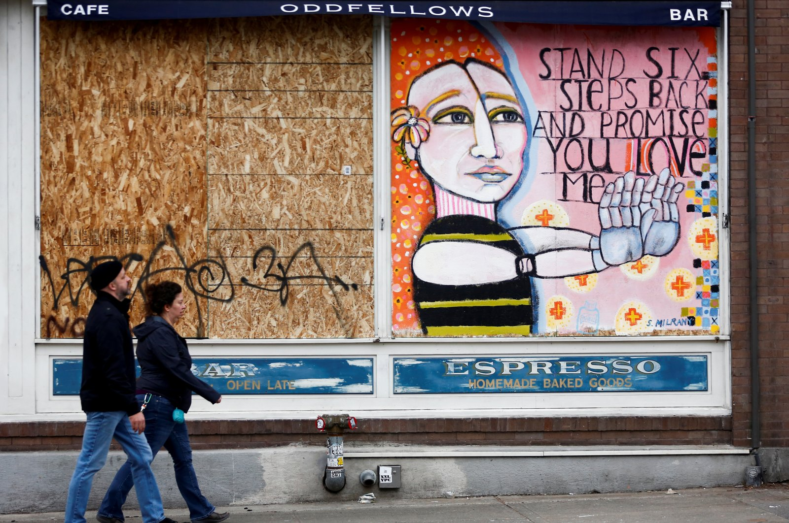 Two people walk by a large mural encouraging six feet of social distancing, Seattle, Washington, March 22, 2020. (REUTERS / Photo)