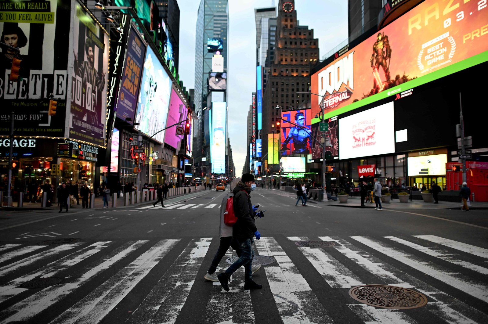 People wearing masks cross the street in Times Square in Manhattan, New York City, Tuesday, March 17, 2020. (AFP Photo)