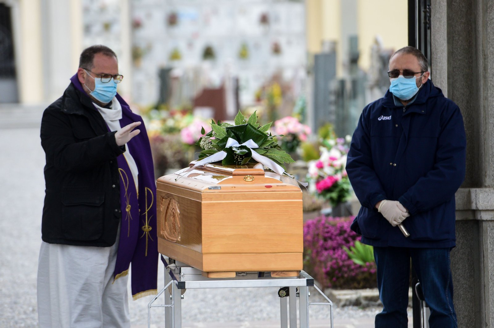 A priest (L), assisted by a pallbearer, both wearing a face mask, gives the last blessing to a deceased person, by a coffin during a funeral service at the cemetery of Bolgare, Lombardy, on March 23, 2020 during the COVID-19 new coronavirus pandemic. (AFP Photo)