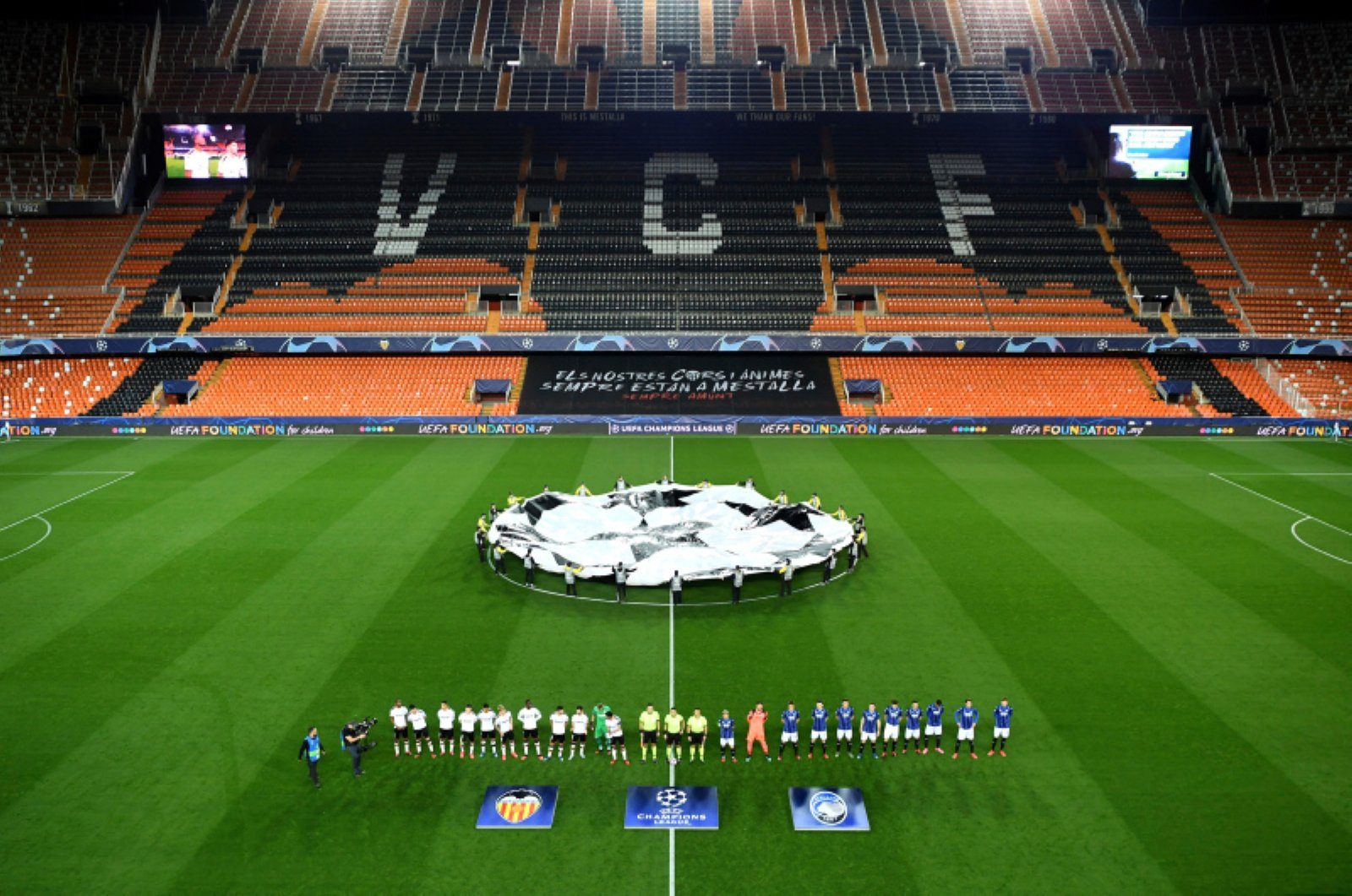Atalanta and Valencia players line up ahead of the Champions League round of 16 second leg soccer match between Valencia and Atalanta in Valencia, Spain, Tuesday March 10, 2020. The match was played in an empty stadium because of the coronavirus outbreak. (UEFA via AP)