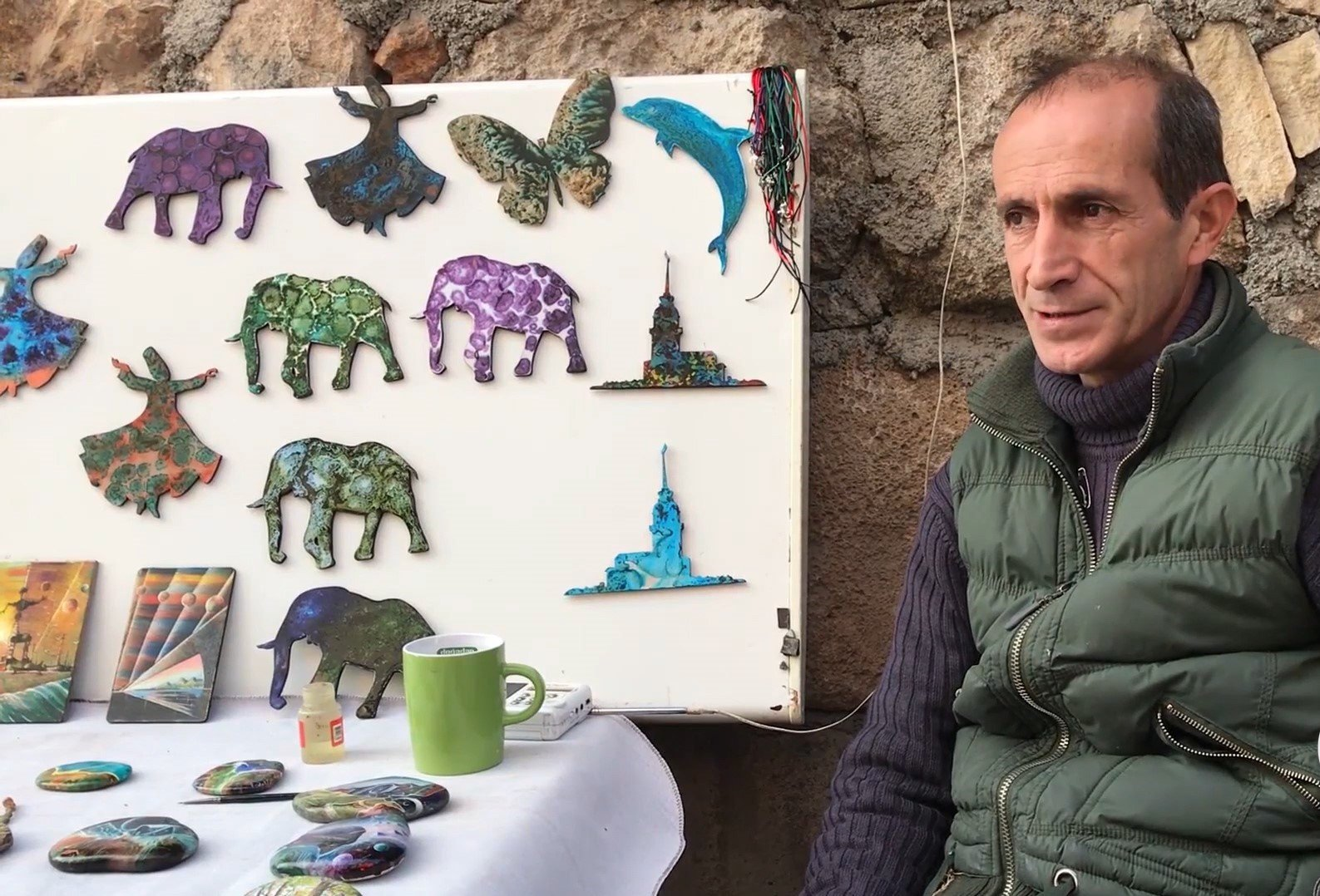 Erdal Parlaklı poses near his booth where he sells his pastoral stone paintings. (AA Photo)