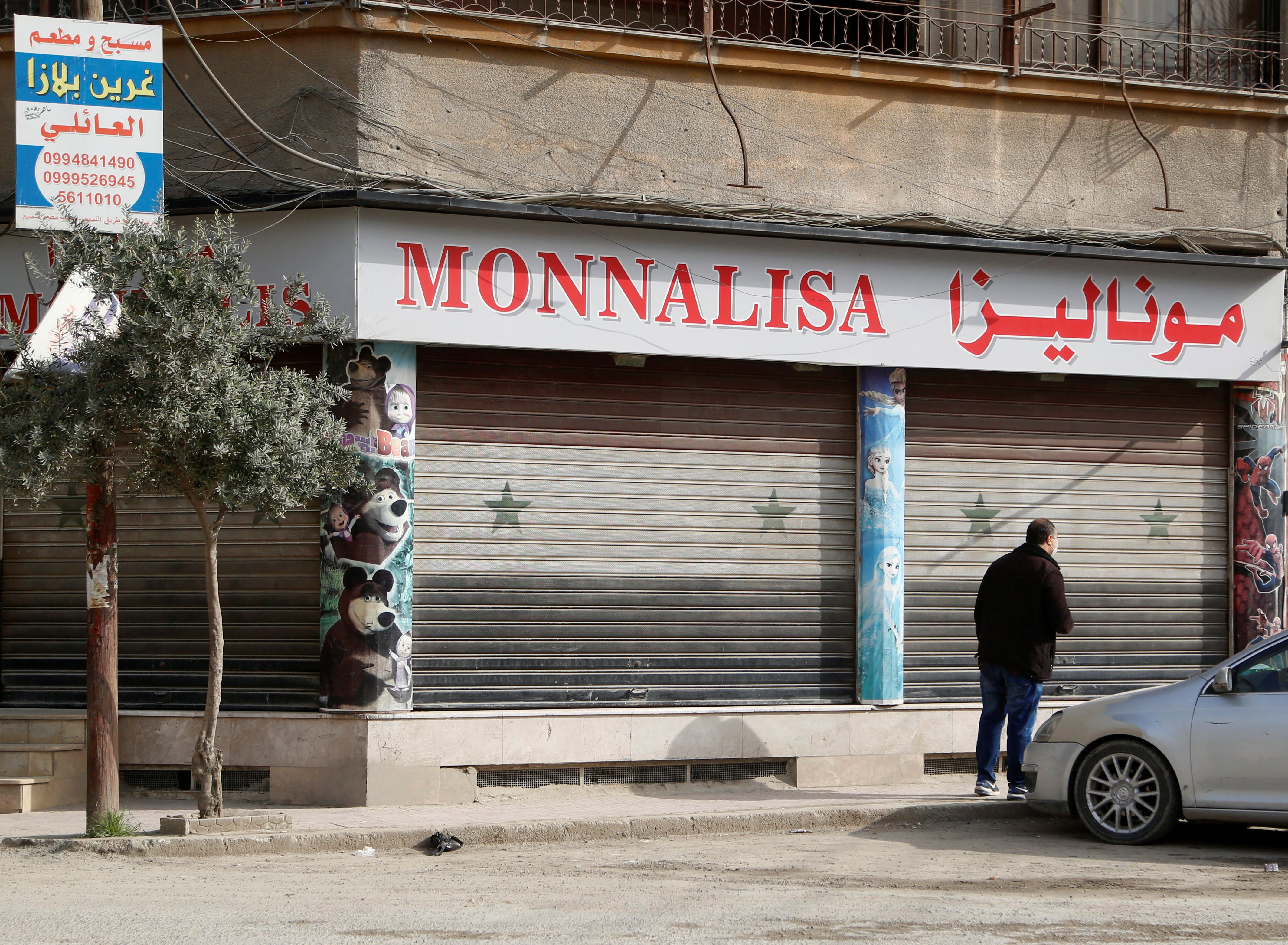 A man stands near a closed shop as Syrian regime confirmed its first case of the coronavirus disease (COVID-19) on Sunday, in Damascus, Syria, Monday, March 23, 2020. (REUTERS)
