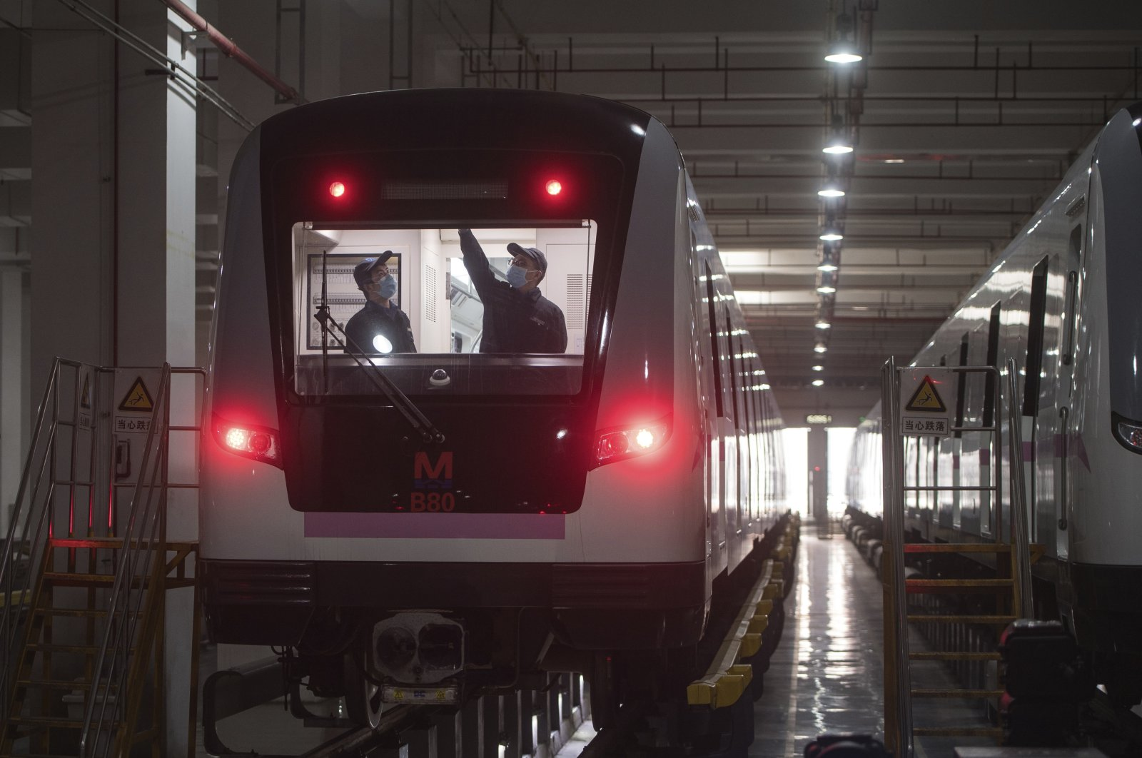 In this March 23, 2020 photo released by Xinhua News Agency, workers prepares a subway train for restoration of public transport in Wuhan, in central China's Hubei province. (Xinhua via AP)