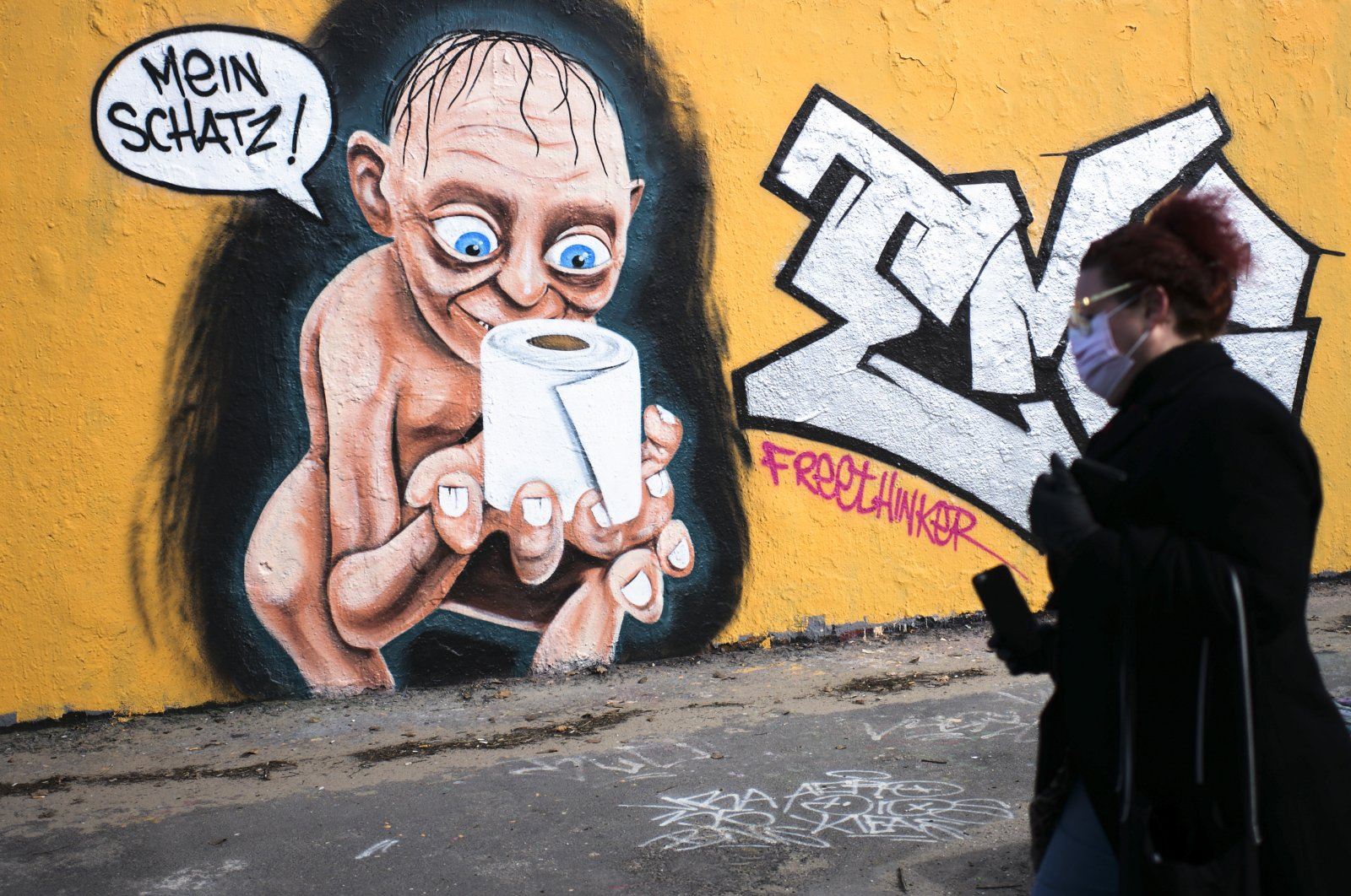 "A woman walks in front of graffiti depicting the character of Gollum from ""Lord of the Rings,"" holding a roll of toilet paper and saying ""My precious,"" in the Mauerpark public park in the Prenzlauer Berg district of Berlin, Germany, Saturday, March 21, 2020. (AP Photo)"